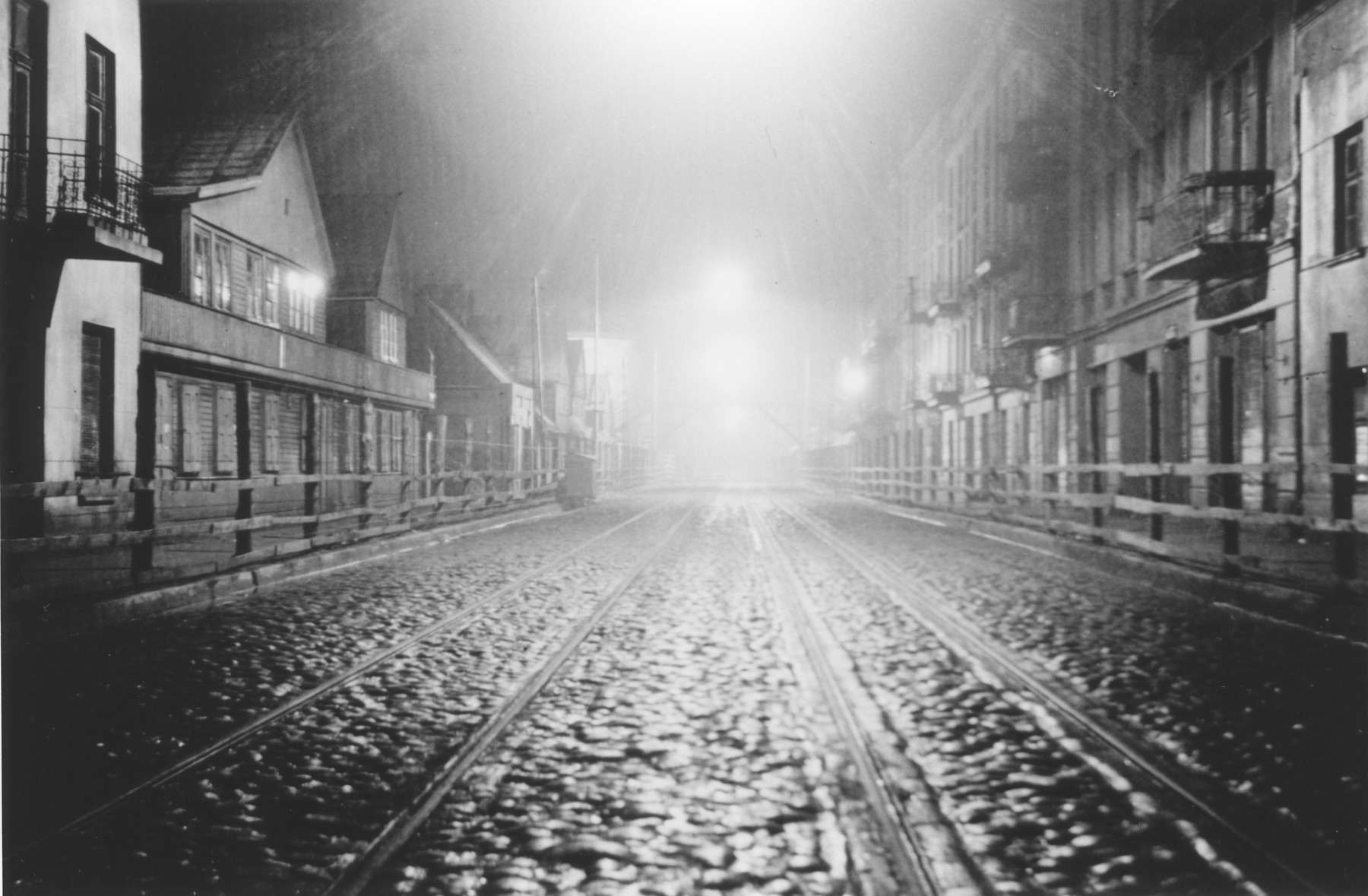 Night-time view of one of the thoroughfares that ran through the Lodz ghetto.  The photograph was probably taken by a member of Police Battalion 101.  The Lodz ghetto was divided into three sectors by two major throughfares which passed through, but did not belong to the Jewish district.  Wooden and barbed wire fences prevented access to these main streets by ghetto residents.  But Jews were allowed to traverse the streets by means of two wooden pedestrian bridges, accessed by steep staircases.   One image from a photograph album belonging to a member of Police Battalion 101.