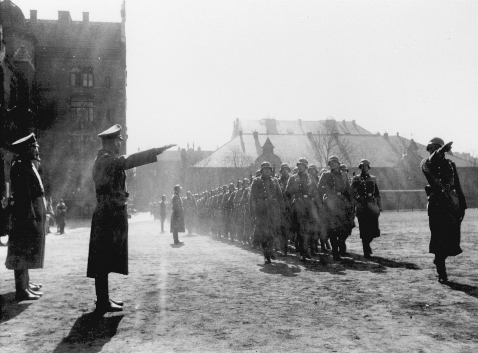 Members of Police Battalion 101 are saluted by their order police officers as they march in formation in Lodz.   One image from a photograph album belonging to a member of Police Battalion 101.