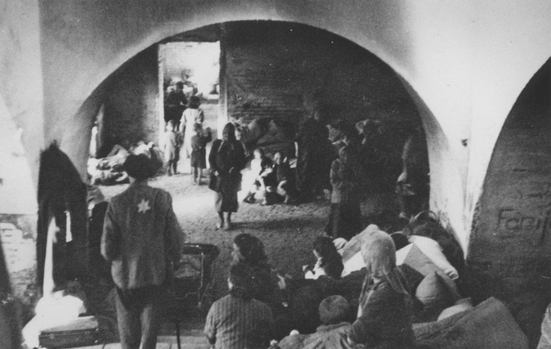 Jews wearing Stars of David sit beneath arched ceilings in a multi-room cellar in an unidentified ghetto.   One image from a photograph album belonging to a member of Police Battalion 101.