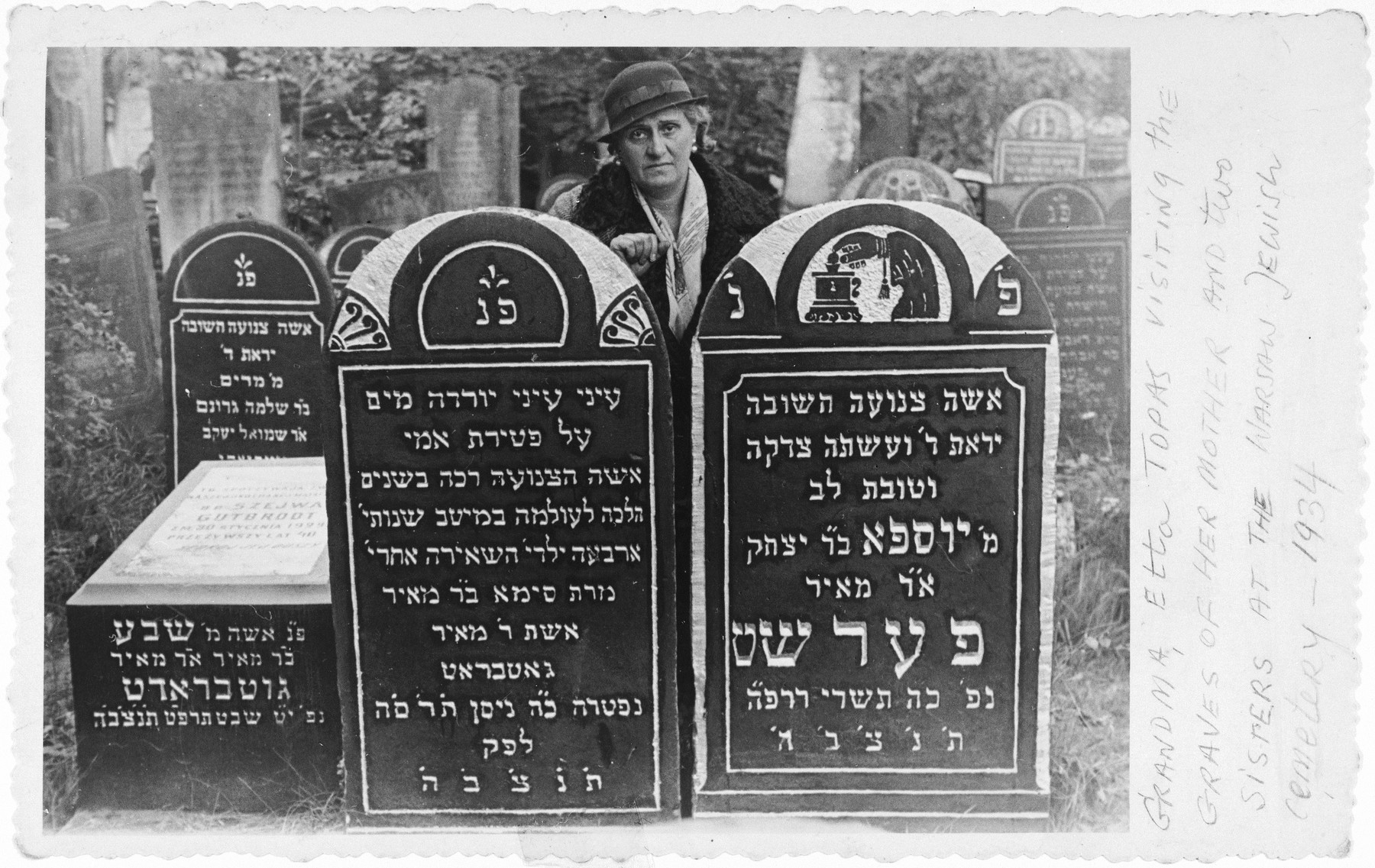A Jewish woman visits the grave of her two sisters in Bialystok.  Pictured above the tombstones is Etta Topas.