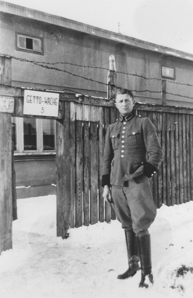 A member of Police Battalion 101 [probably Bernhardt Colberg] poses at the entrance of guard post #5 in the Lodz ghetto.  One image from a photograph album belonging to a member of Police Battalion 101.