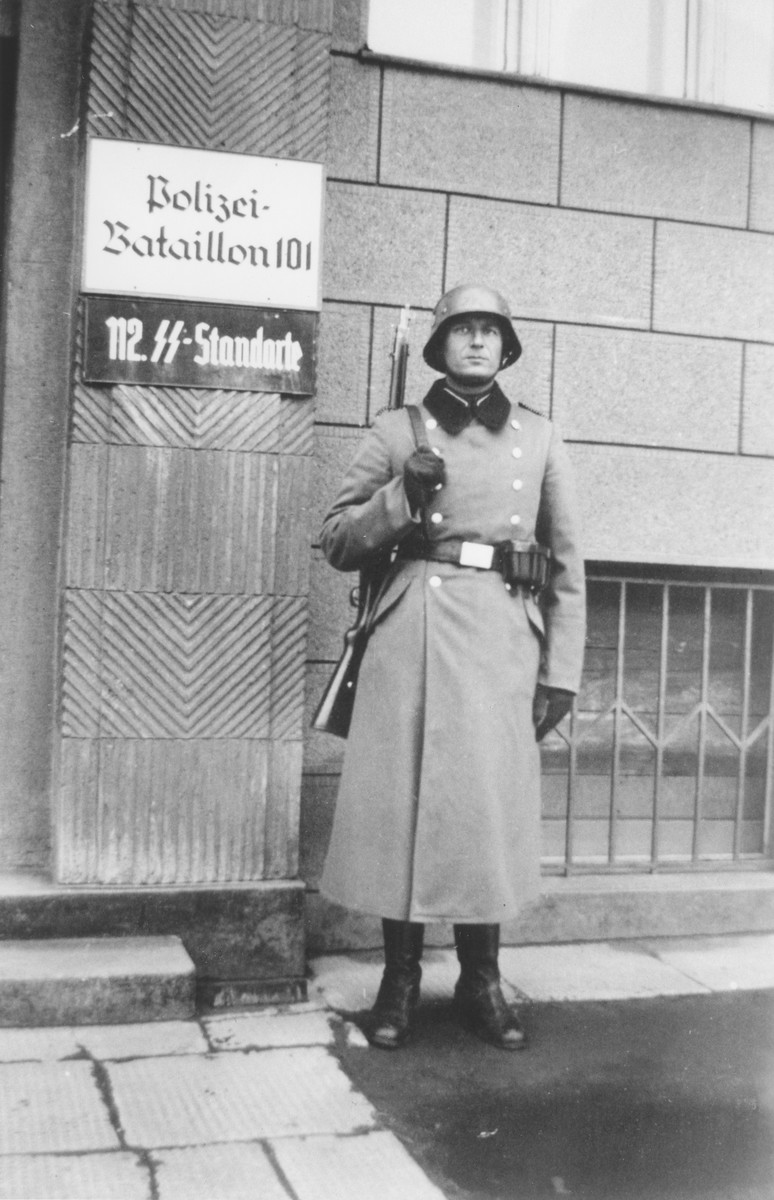 Bernhardt Colberg, a member of Police Battalion 101 poses in front of their headquarters in the vicinity of Lodz.  One image from a photograph album belonging to a member of Police Battalion 101.