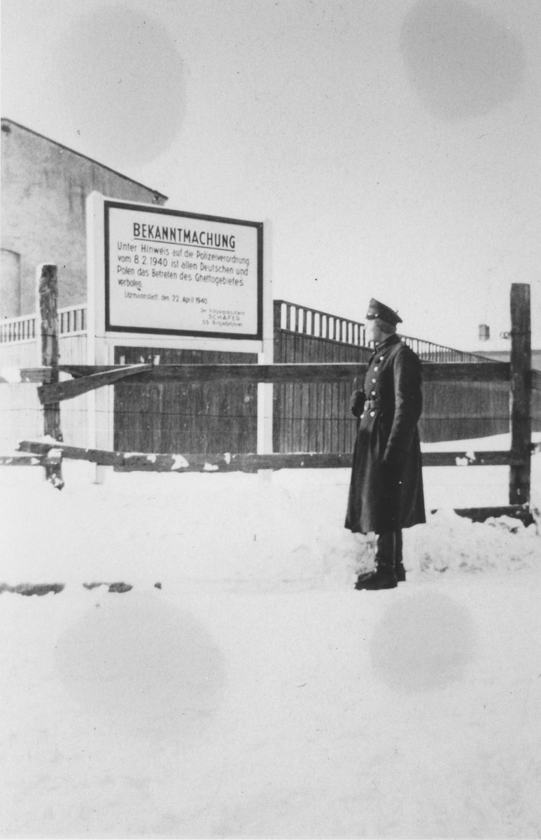 "A member of Police Battalion 101 poses next to a large sign marking the entrance to the Lodz ghetto.  The German text of the sign, which is dated April 22, 1940, reads: ""Announcement: In accordance with a police order of February 8, 1940, all Germans and Poles are forbidden entry into the ghetto area.""   One image from a photograph album belonging to a member of Police Battalion 101."