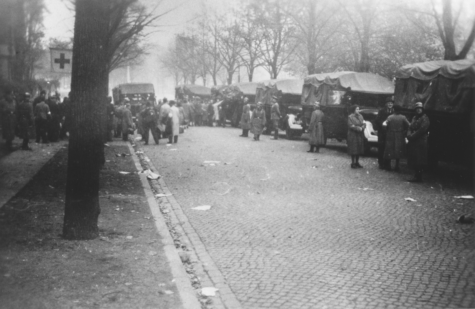 Members of Police Battalion 101 stand in front of a convoy of trucks that have been parked across from an assembly point on the Moorweidenstrasse in Hamburg, where Germans who are the victims of Allied air raids are gathered prior to their evacuation.  One image from a photograph album belonging to a member of Police Battalion 101.