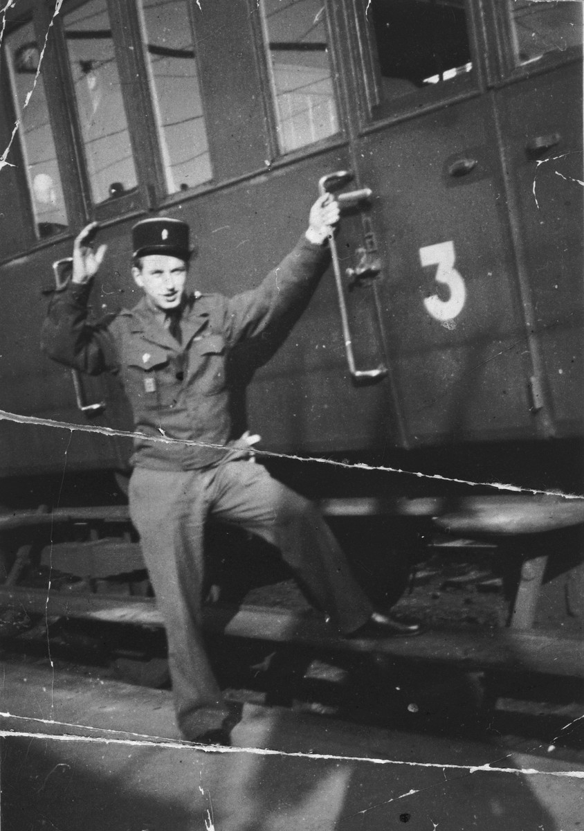 German Jewish refugee Ernest Marx waves from the side of a train.  He is wearing the uniform of the Chasseur Alpin unit of the French Maquis resistance.