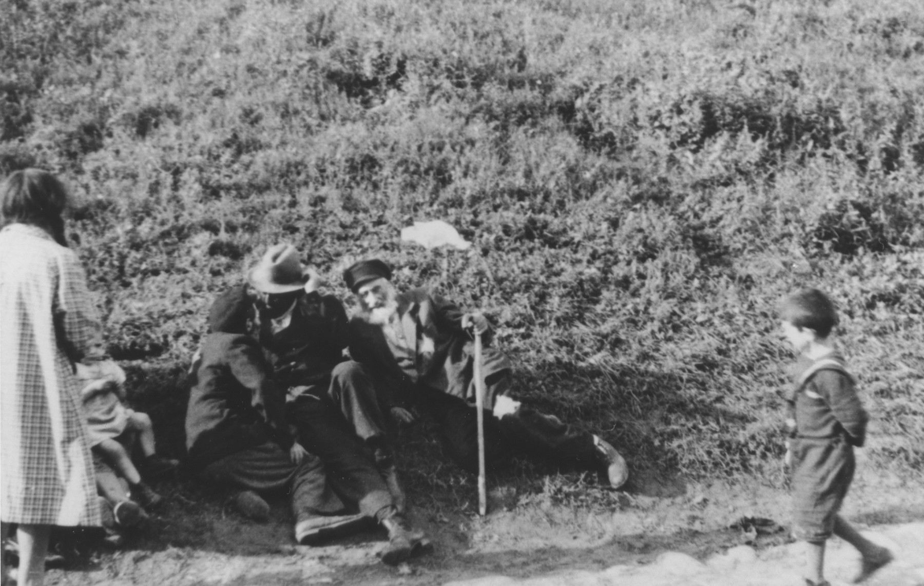 A boy dressed in a sailor suit walking along a road views a Jewish family sitting in the grass at the side of the road.   One image from a photograph album belonging to a member of Police Battalion 101.