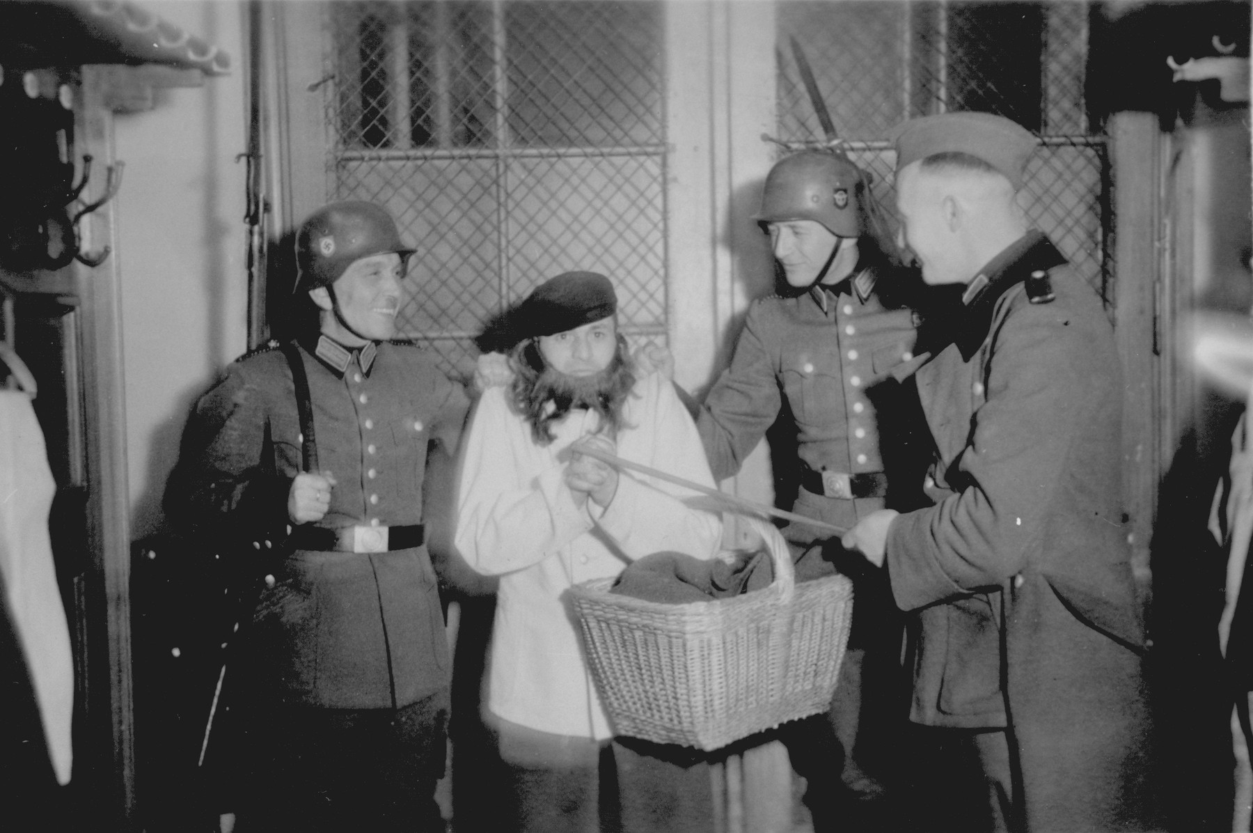 [Mock arrest of a comrade dressed up as a bearded Jewish peddlar by members of Police Battalion 101].  One image from a photograph album belonging to a member of Police Battalion 101.