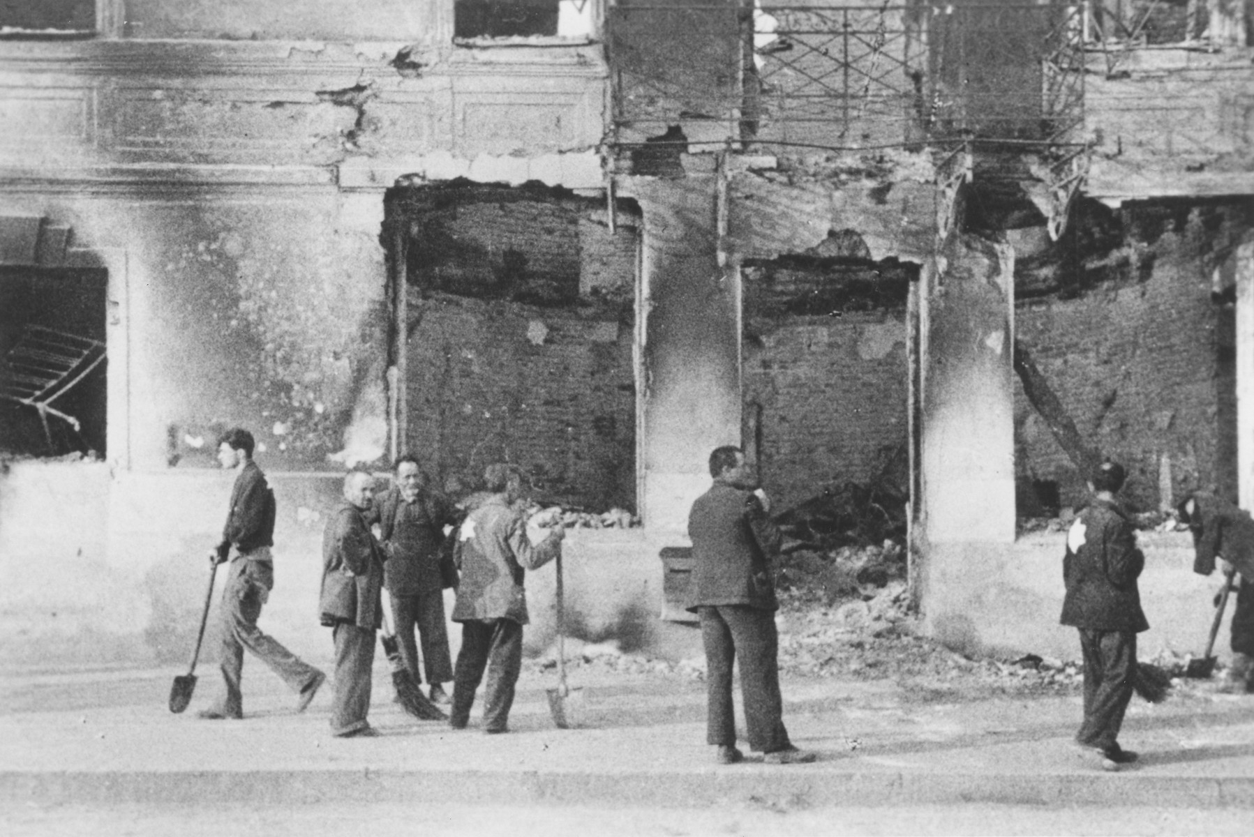 Jews at forced labor clearing rubble from a bombed out building.  The photograph was probably taken by a member of Police Battalion 101.   One image from a photograph album belonging to a member of Police Battalion 101.
