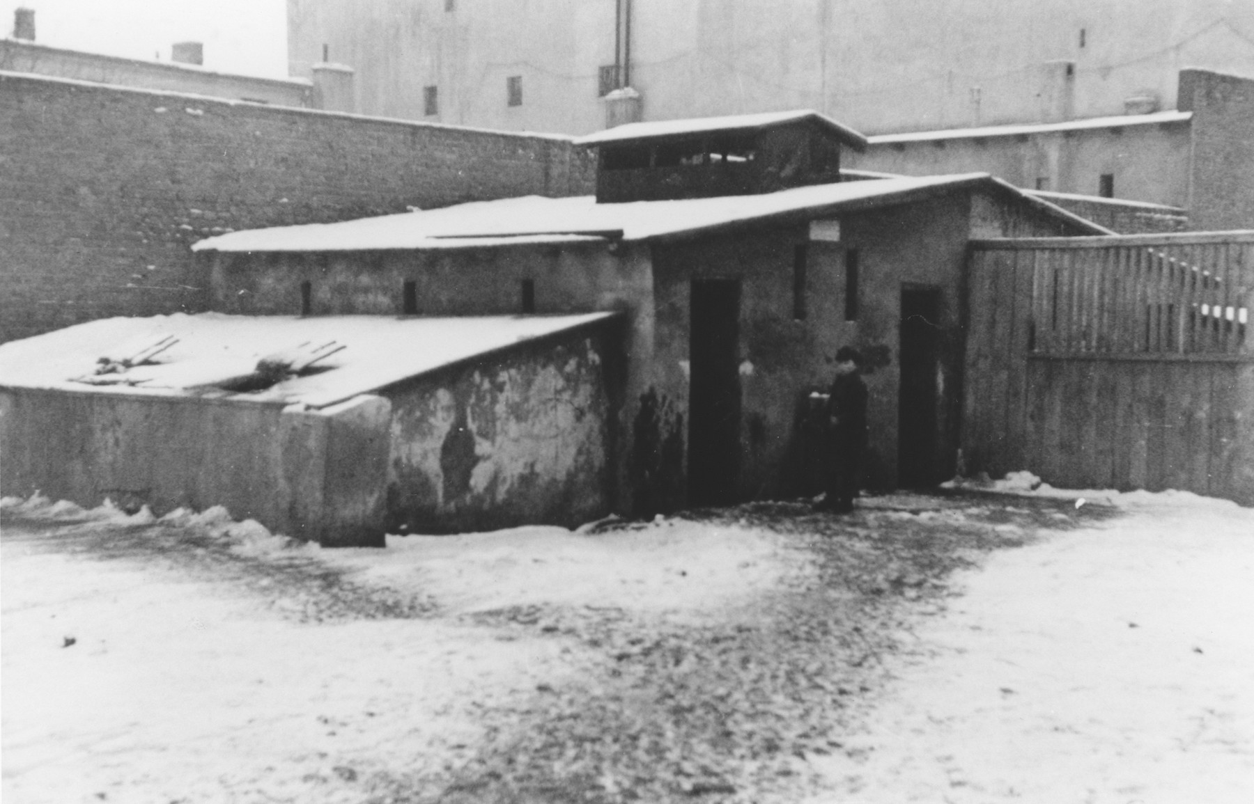 A Jew (perhaps a policeman) stands outside a low slung building in the Lodz ghetto.  The photograph was probably taken by a member of Police Battalion 101.   One image from a photograph album belonging to a member of Police Battalion 101.