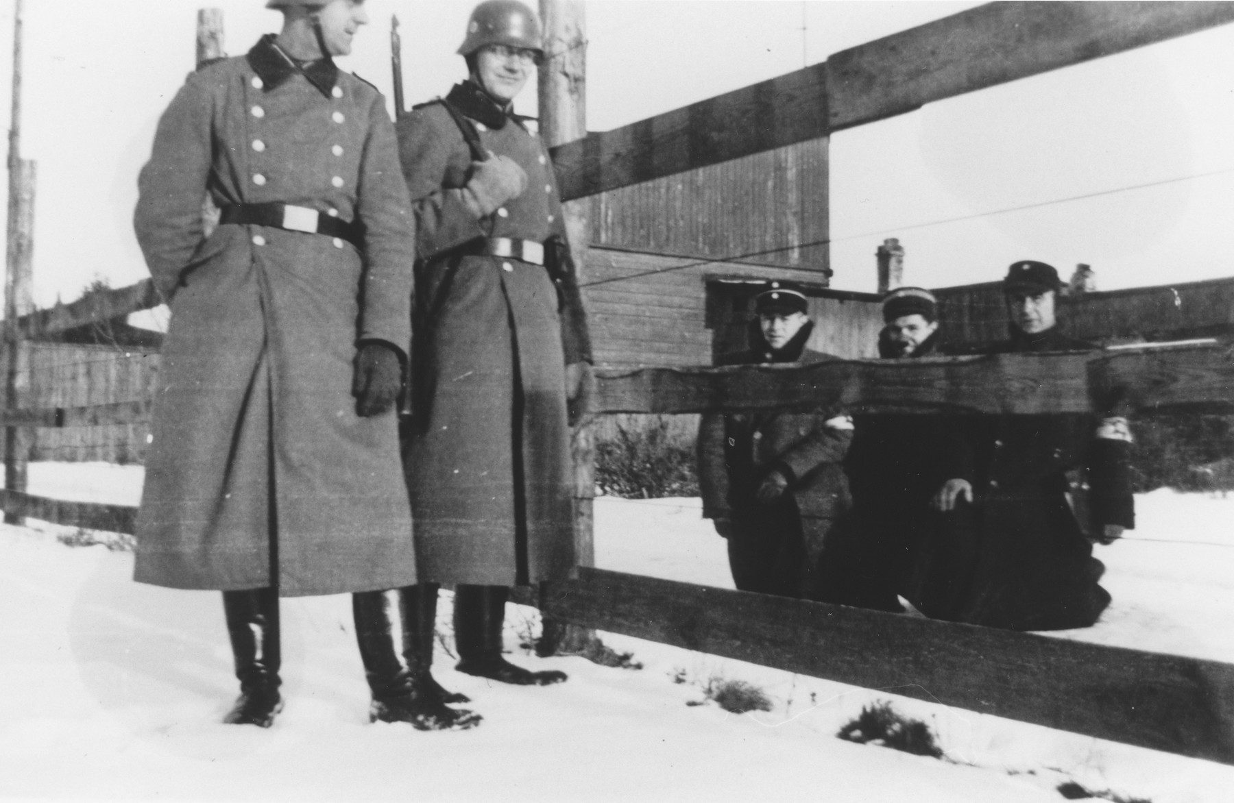 Two members of Police Battalion 101 who are guarding the perimeter of the Lodz ghetto, view three Jewish policemen kneeling opposite them on the other side of the fence.   One image from a photograph album belonging to a member of Police Battalion 101.