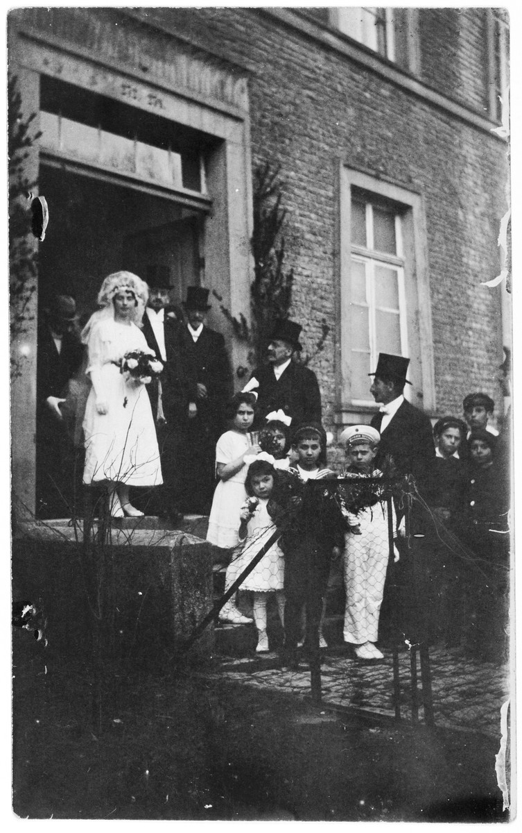 Bertha Steinberger and Siegmund Marx leave the synagogue after their wedding ceremony, accompanied by a group of small children.