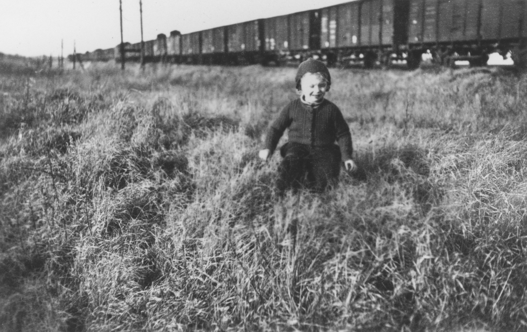 A child runs through the grass in front of a freight train.  [The child may be the visiting son or daughter of a member of Police Battalion 101]   One image from a photograph album belonging to a member of Police Battalion 101.