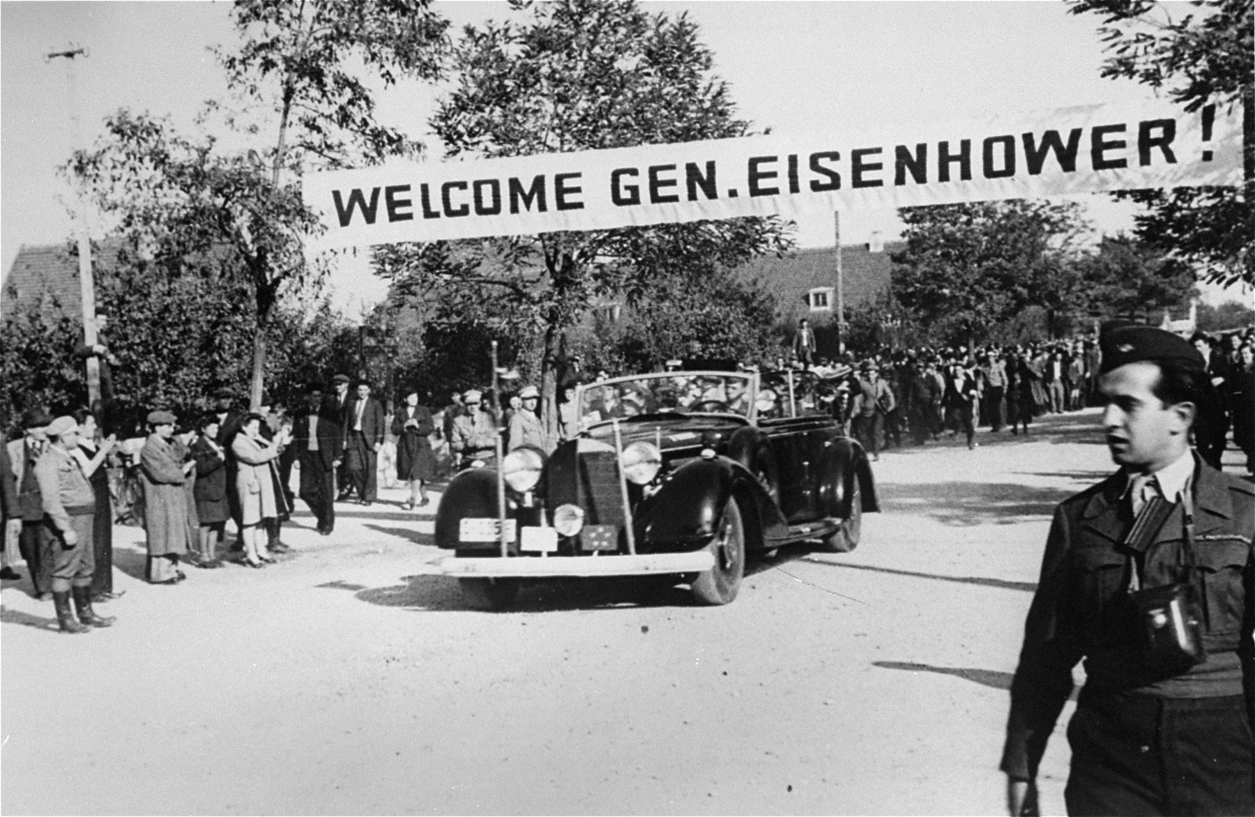 Neu Freimann residents greet General Dwight Eisenhower as his car drives into the displaced persons' camp.  Eisenhower's visits to Neu Freimann and other displaced persons' camps in the fall of 1945 was prompted by a strongly worded cable he received  from President Truman directing him to institute reforms to improve living conditions of displaced Jews in the American zone of occupation.