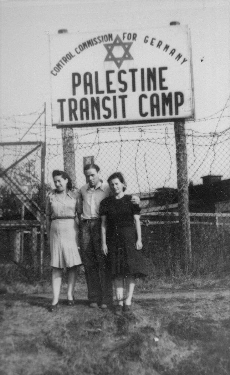 """Three Jewish DPs pose in front of the entrance to the Palestine Transit Camp in Bremen, where they await transport to Palestine.    The Polish caption on the back of the photo reads: """"A momento from G. Tikocinska  Bocholt, 21 August, 1947."""""""