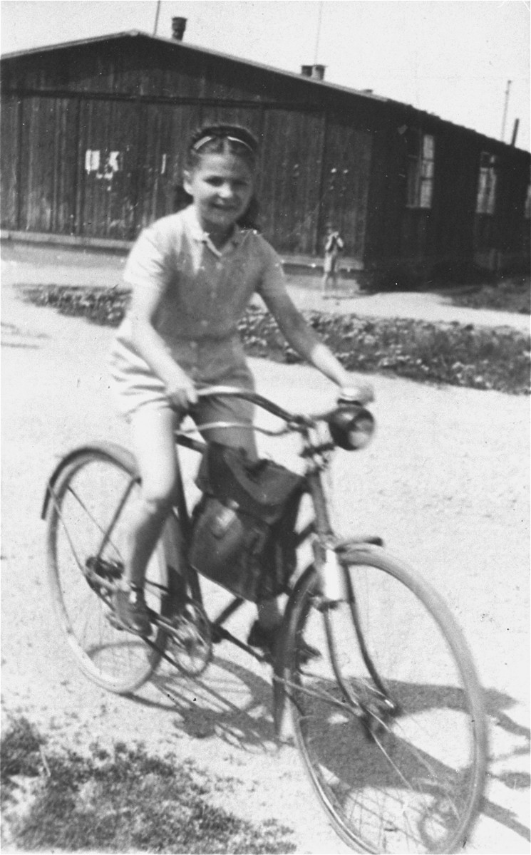 Frima Gleiser rides a bicycle in the Pocking (Schlupfing) displaced persons camp.