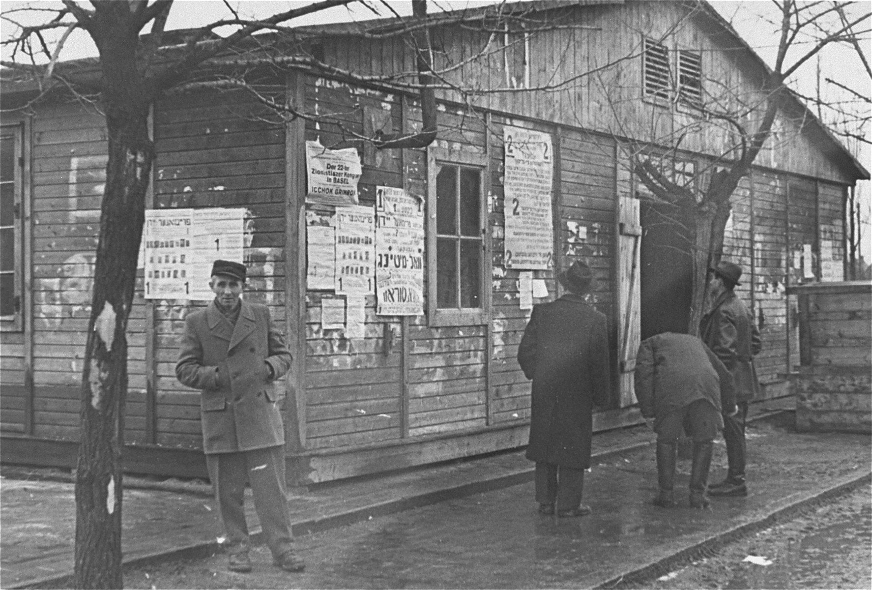 View of a wooden barracks on which numerous notices have been plastered at the Neu Freimann displaced persons camp.