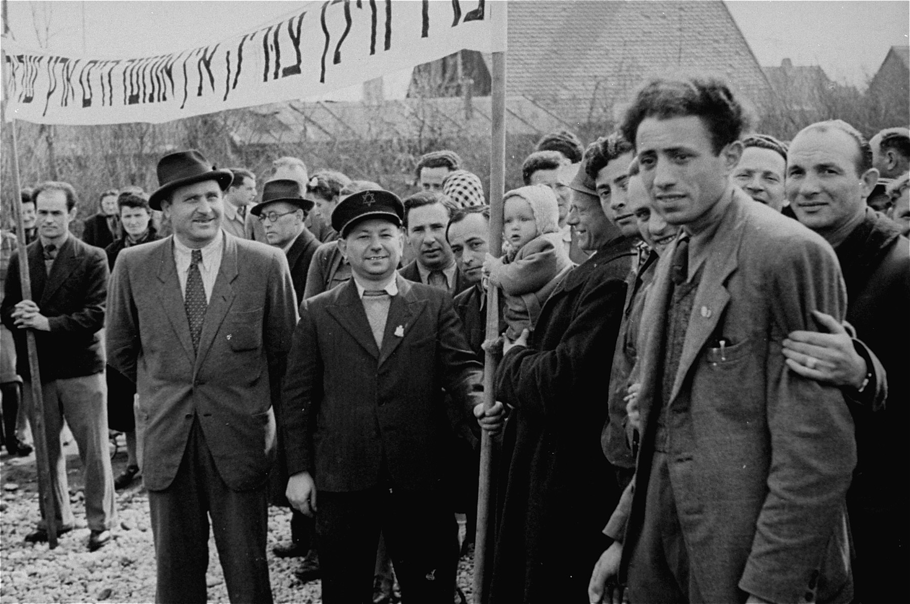 """Jewish DPs  participate in a demonstration calling for unrestricted immigration to Palestine at the Neu Freimann displaced persons camp.  The text of the Yiddish banner reads: """"We want to go back to our home in the Land of Israel."""""""