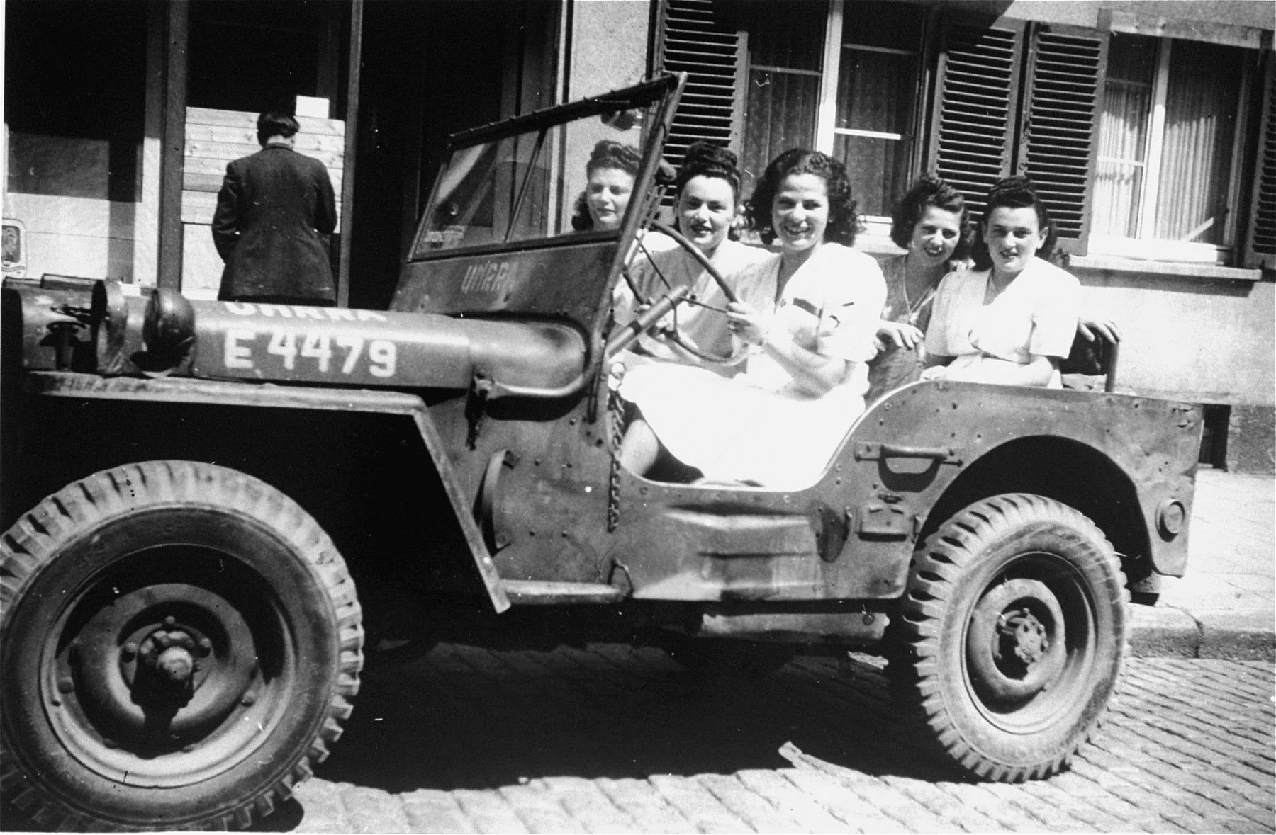 UNRRA nurses sit in a jeep outside the Stuttgart displaced persons camp.