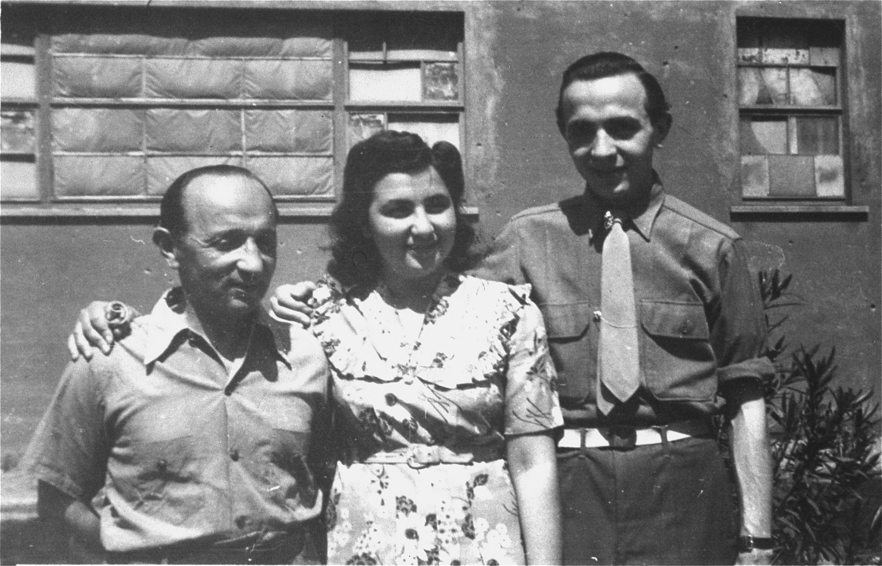 Three Jewish DPs pose outside at the Cinecitta displaced persons camp in Rome.  From left to right are Edward Arzt and his children Evelyn (later Bergl), and Heinz.