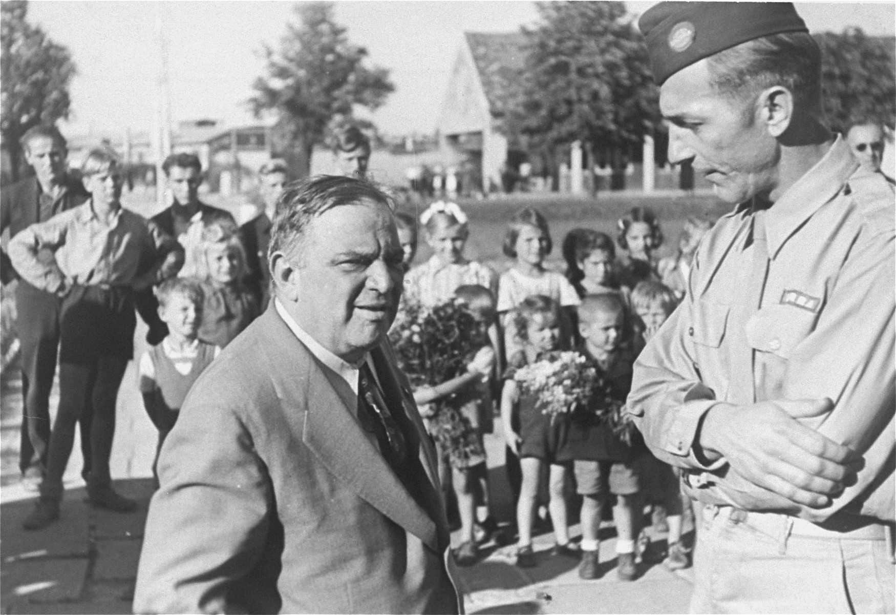 UNRRA Director General Fiorello LaGuardia converses with an unidentified official during a visit to the Neu Freimann displaced persons camp.  In the background a group of children stand in formation.