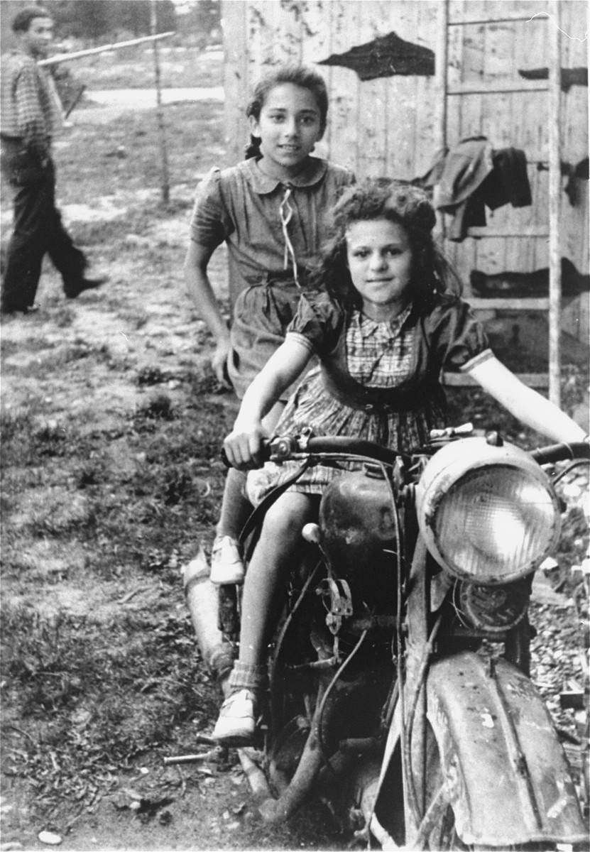Two girls pose on a motorcycle in the Pocking (Schlupfing) displaced persons camp.