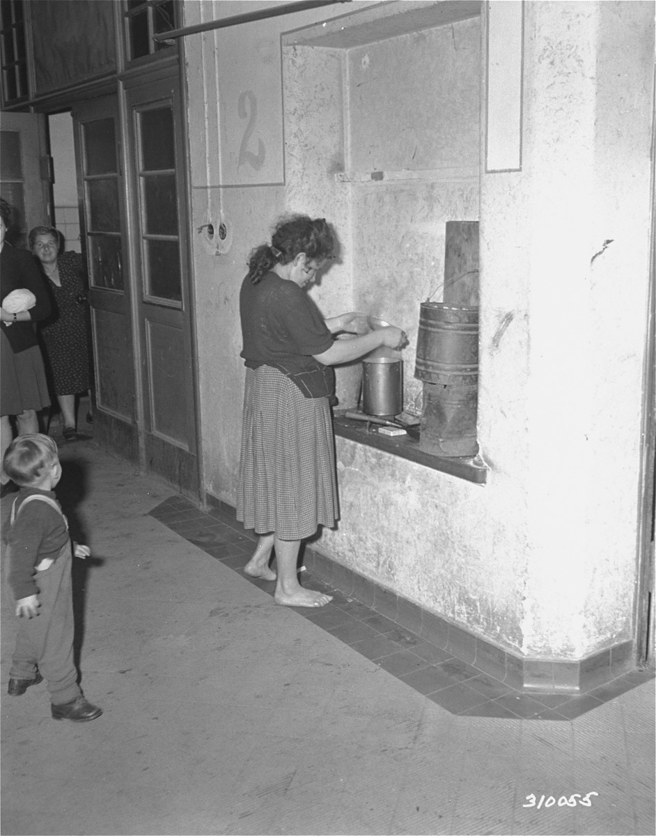 A Jewish woman cooks her dinner in what used to be a gun rack at the displaced persons camp in Wetzlar.