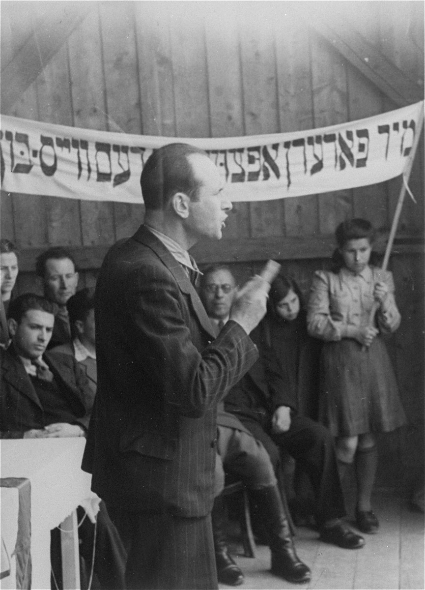 "A DP spokesman delivers a speech at a demonstration calling for unrestricted immigration to Palestine.  The text of the Yiddish banner reads: ""We demand the repeal of the [British] White Paper."""