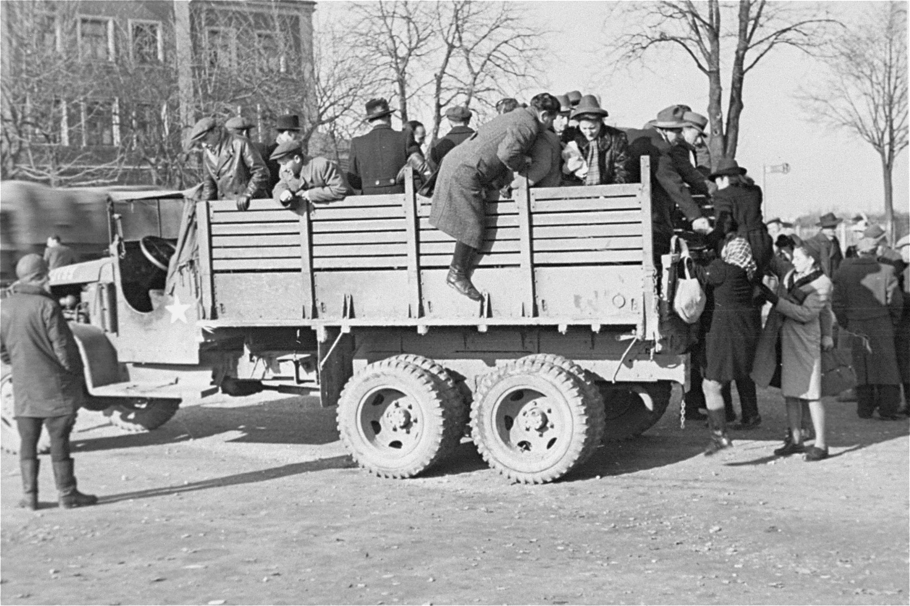 Departing Jewish DPs climb onto the back of a truck at a displaced persons camp in Germany.