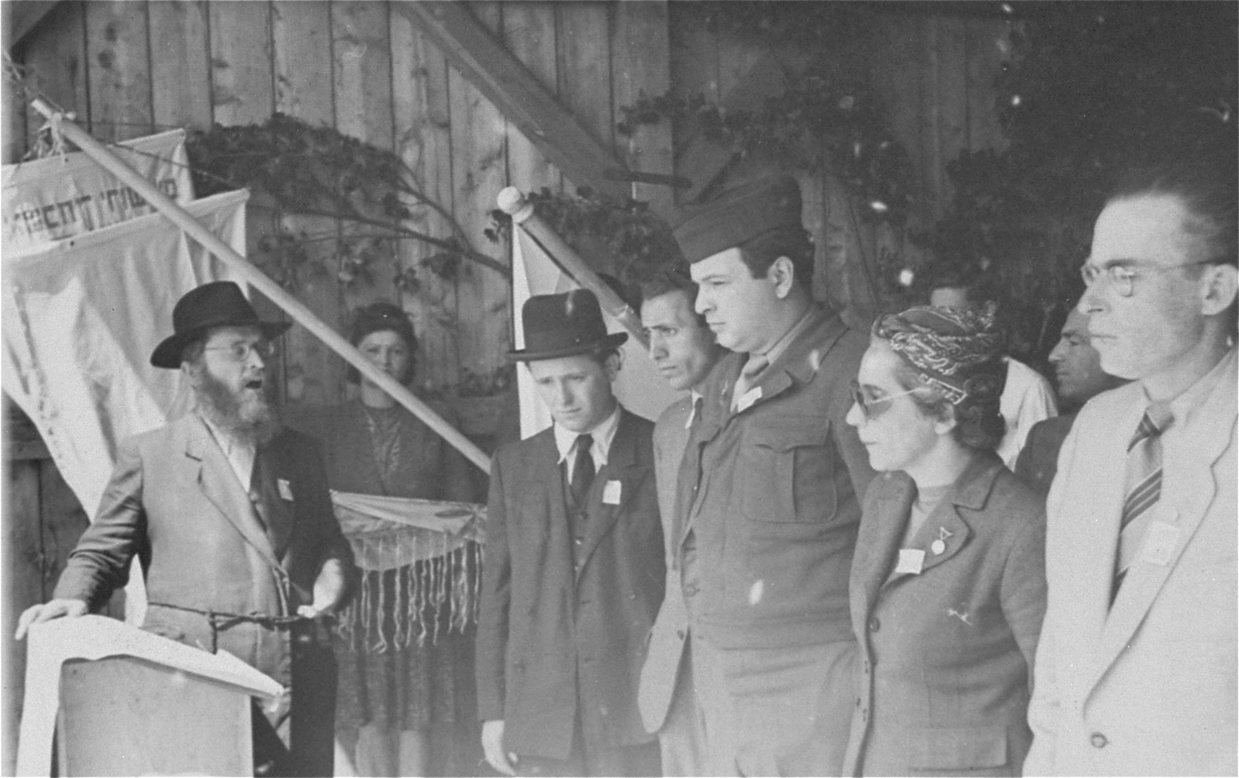 Director Saul Sorrin and other DP camp leaders listen as a cantor sings a hymn at a ceremony in the Neu Freimann displaced persons camp.