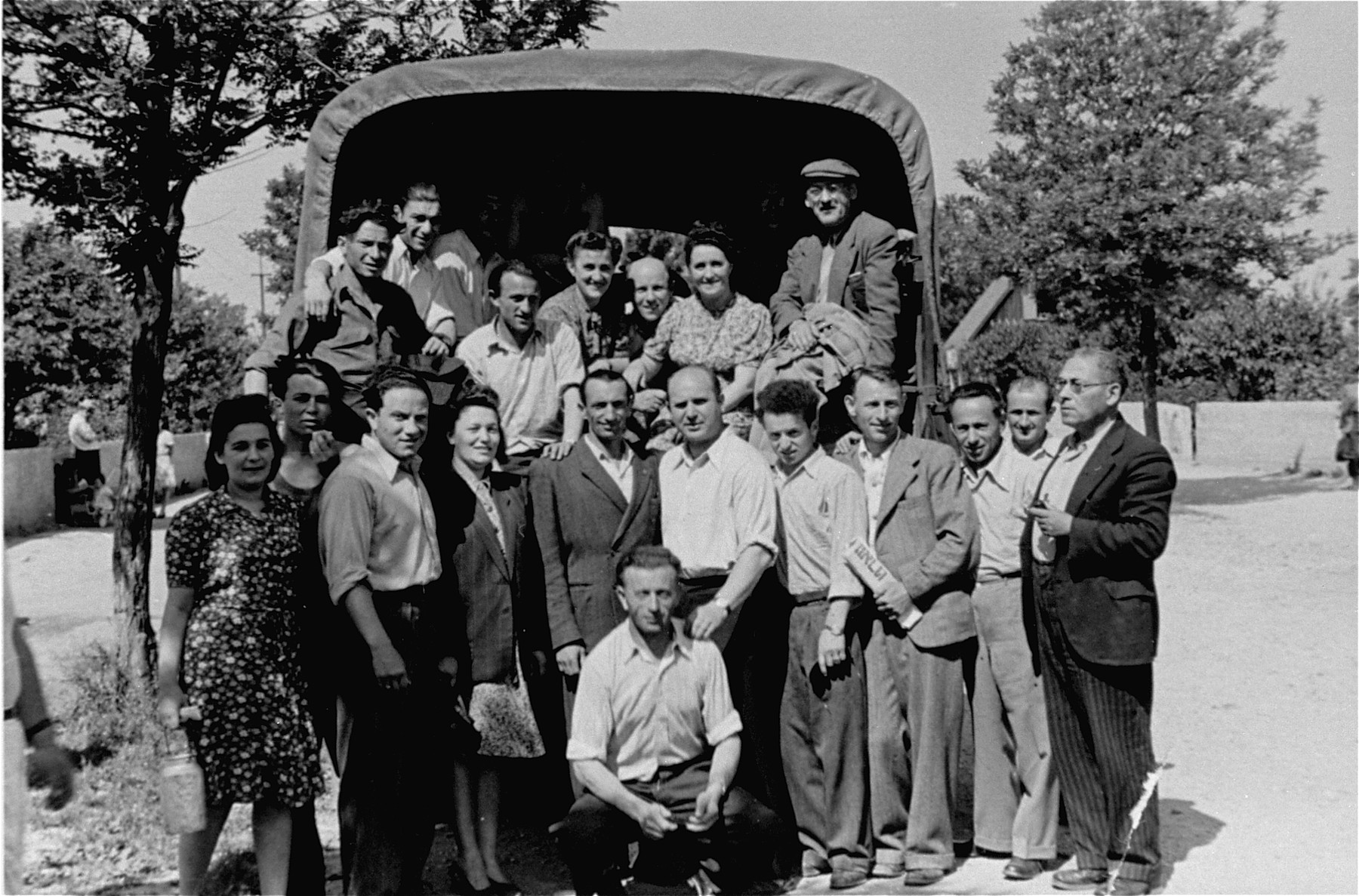 Departing DPs pose in front of a truck at a displaced persons camp in Germany.