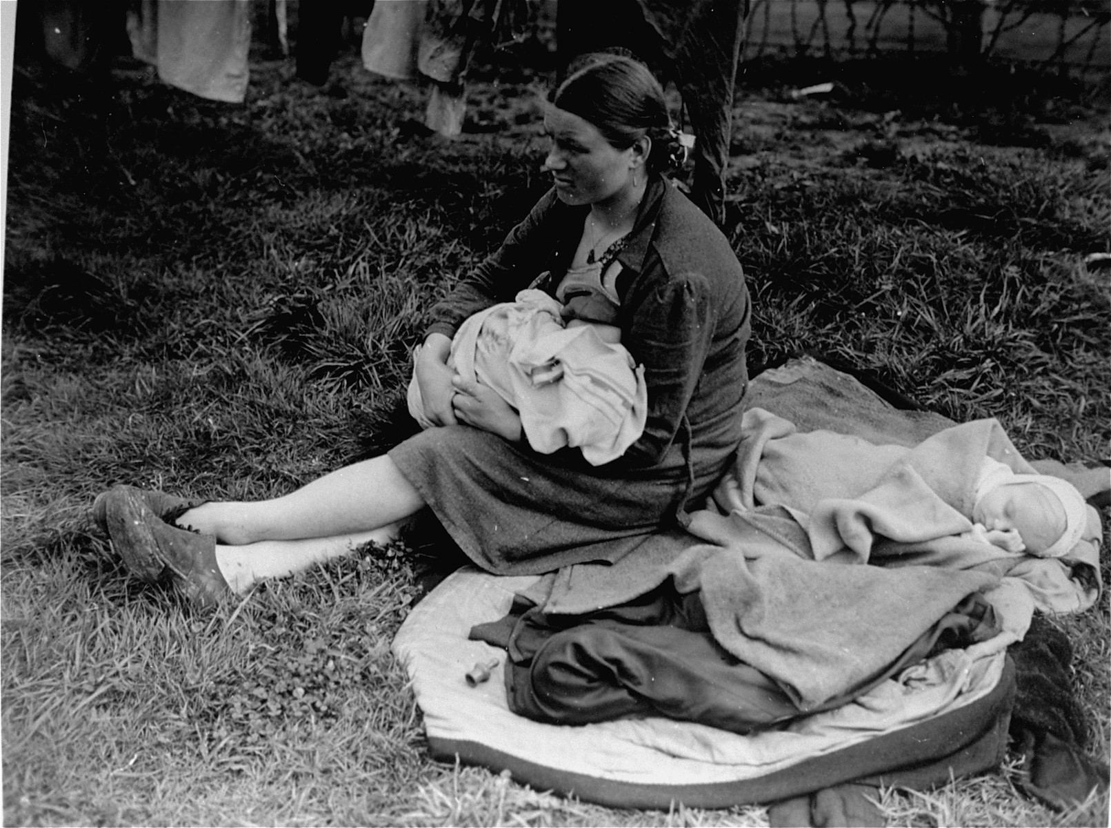 A Russian displaced person nurses one of her babies.