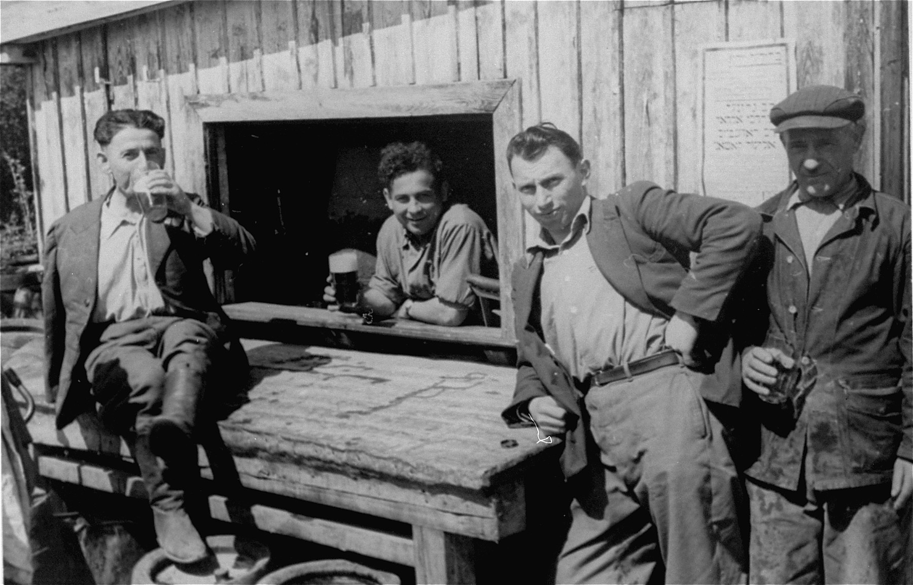 Jewish DPs drinking beer outside a canteen in the Neu Freimann displaced persons camp.