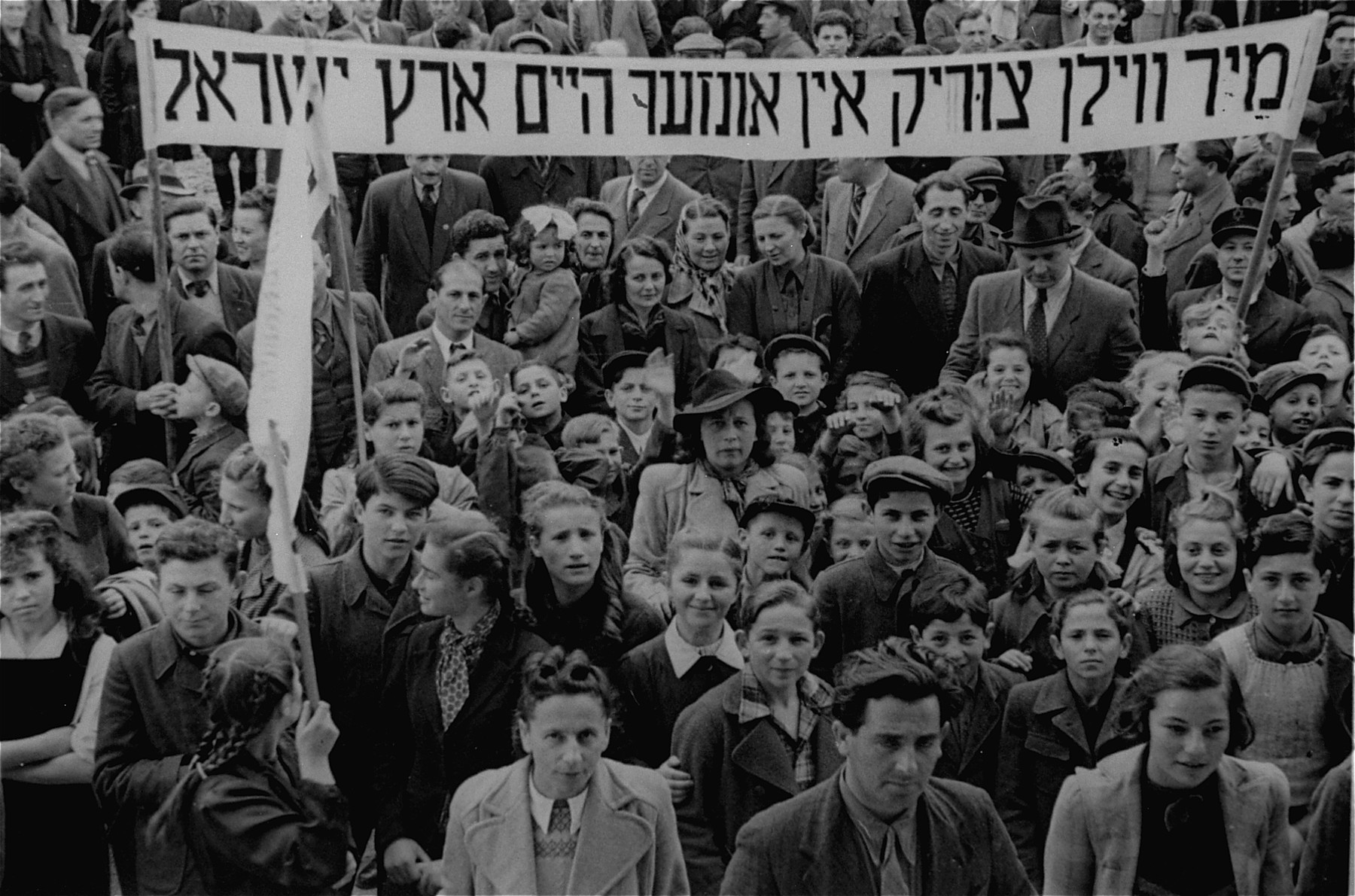 "Jewish DPs at the Neu Freimann displaced persons camp participate in a demonstration calling for unrestricted immigration to Palestine.  The text of the Yiddish banner reads: ""We want to go back to our home in the Land of Israel.""  One of those pictured amongst the crowd is Franz Kaunty."