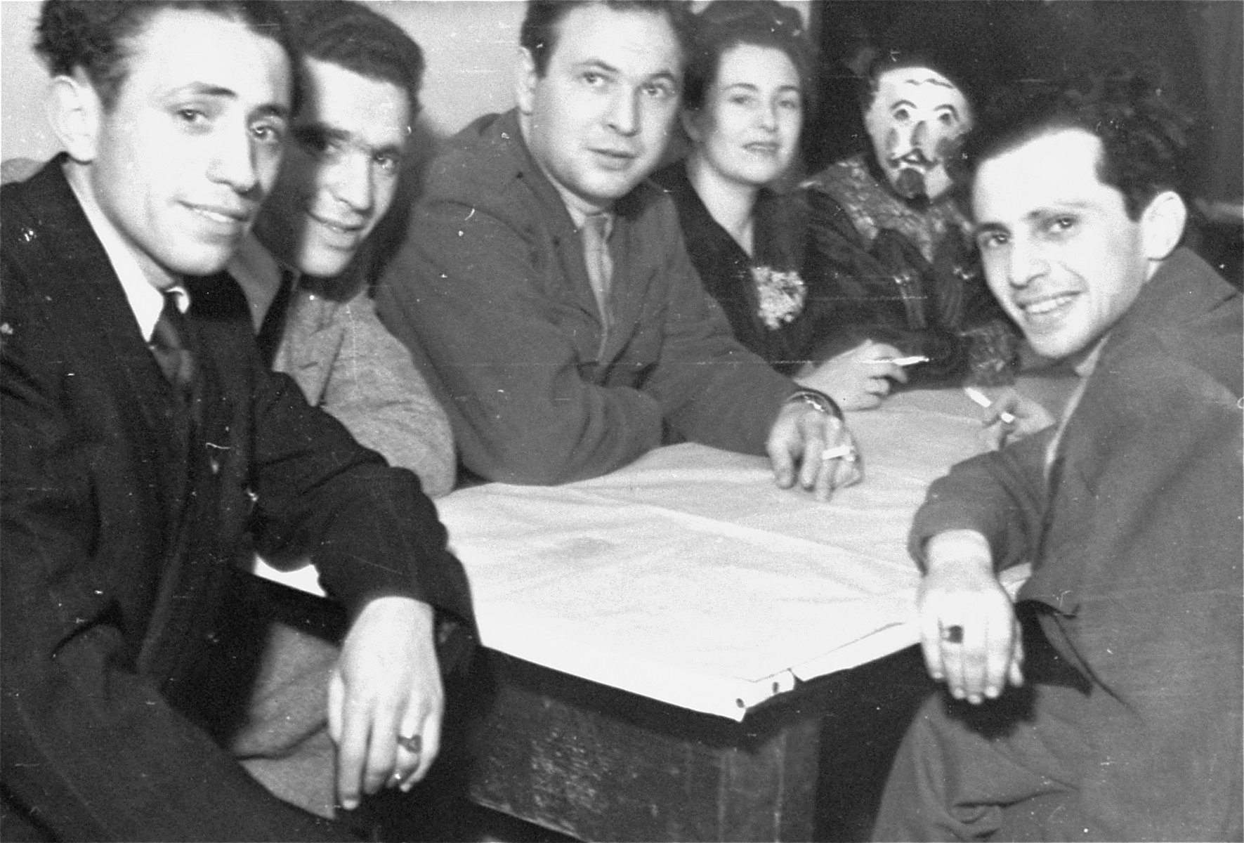 Neu Freimann director Saul Sorrin (center) sits at a table with a group of Jewish DPs at the Neu Freimann displaced persons camp.