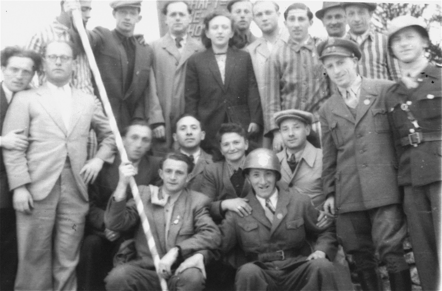 Jewish men, some in concentration camp uniform gather in the Pocking displaced persons camp.   Alexander Contract holds the Israeli flag.