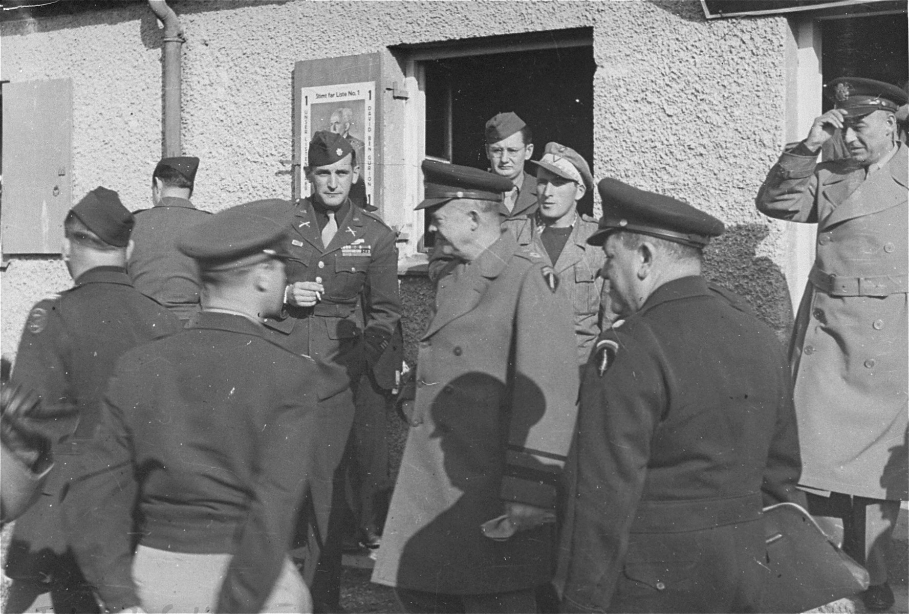 General Dwight Eisenhower walks out of the camp synagogue during an official tour of the Neu Freimann displaced persons' camp.  Eisenhower's visits to Neu Freimann and other displaced persons' camps in the fall of 1945 was prompted by a strongly worded cable he received  from President Truman directing him to institute reforms to improve living conditions of displaced Jews in the American zone of occupation.