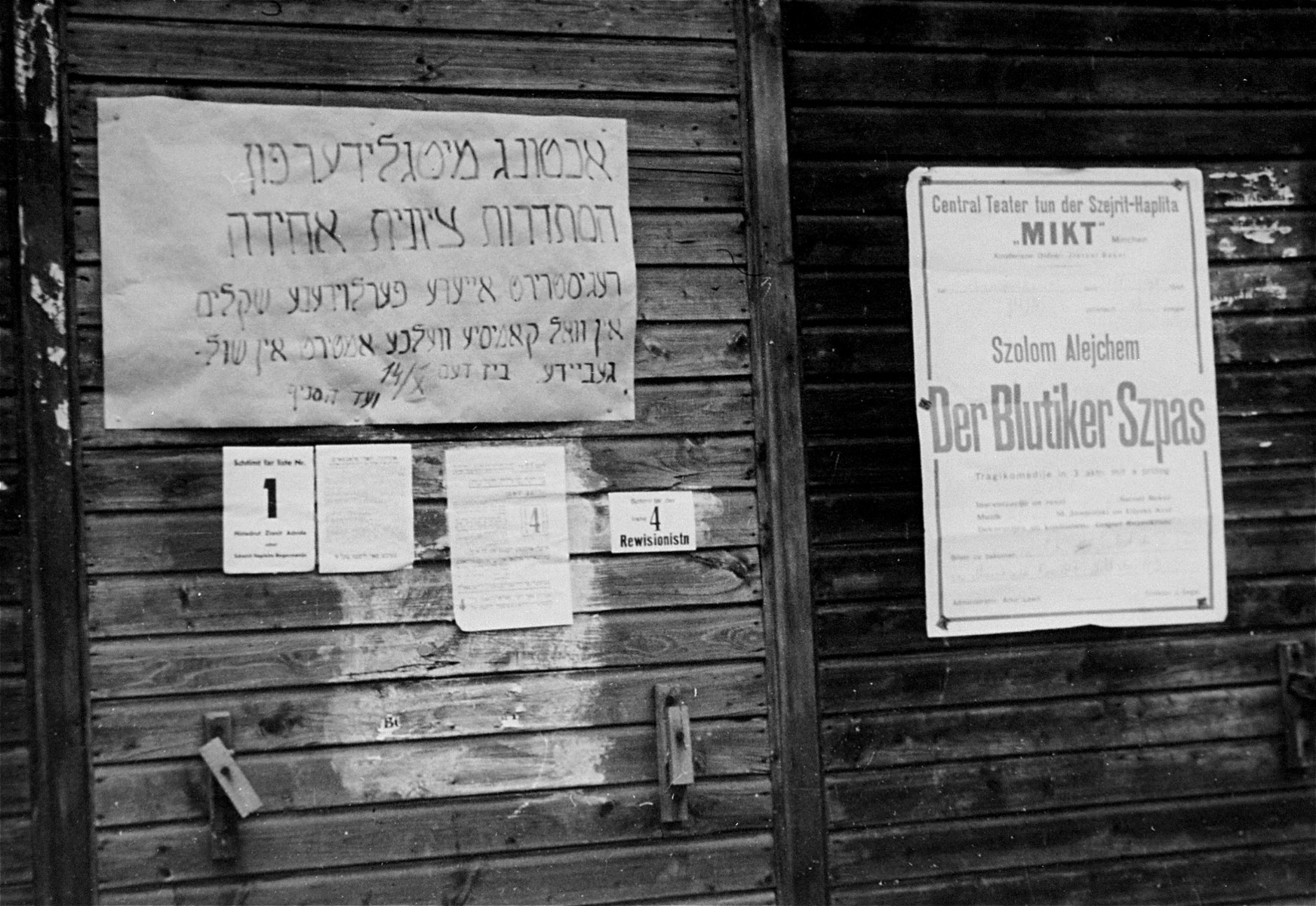 Notices posted on the wall of a barracks at the Neu Freimann displaced persons camp.  The poster on the left is addressed to members of the united Zionist labor organization.  The one on the right advertises the performance of a Yiddish play by Sholem Aleichem.