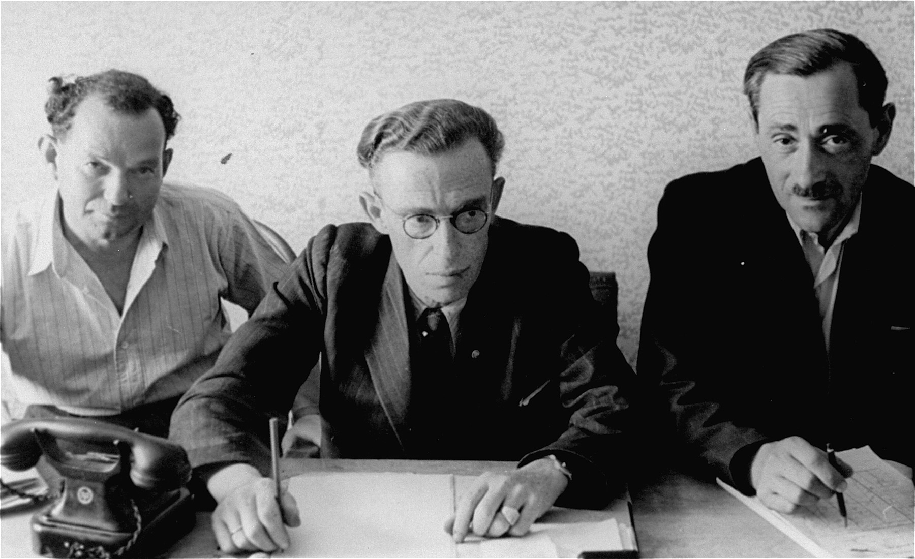 Close-up portrait of three administrators in an office at an unidentified displaced persons camp in Germany.