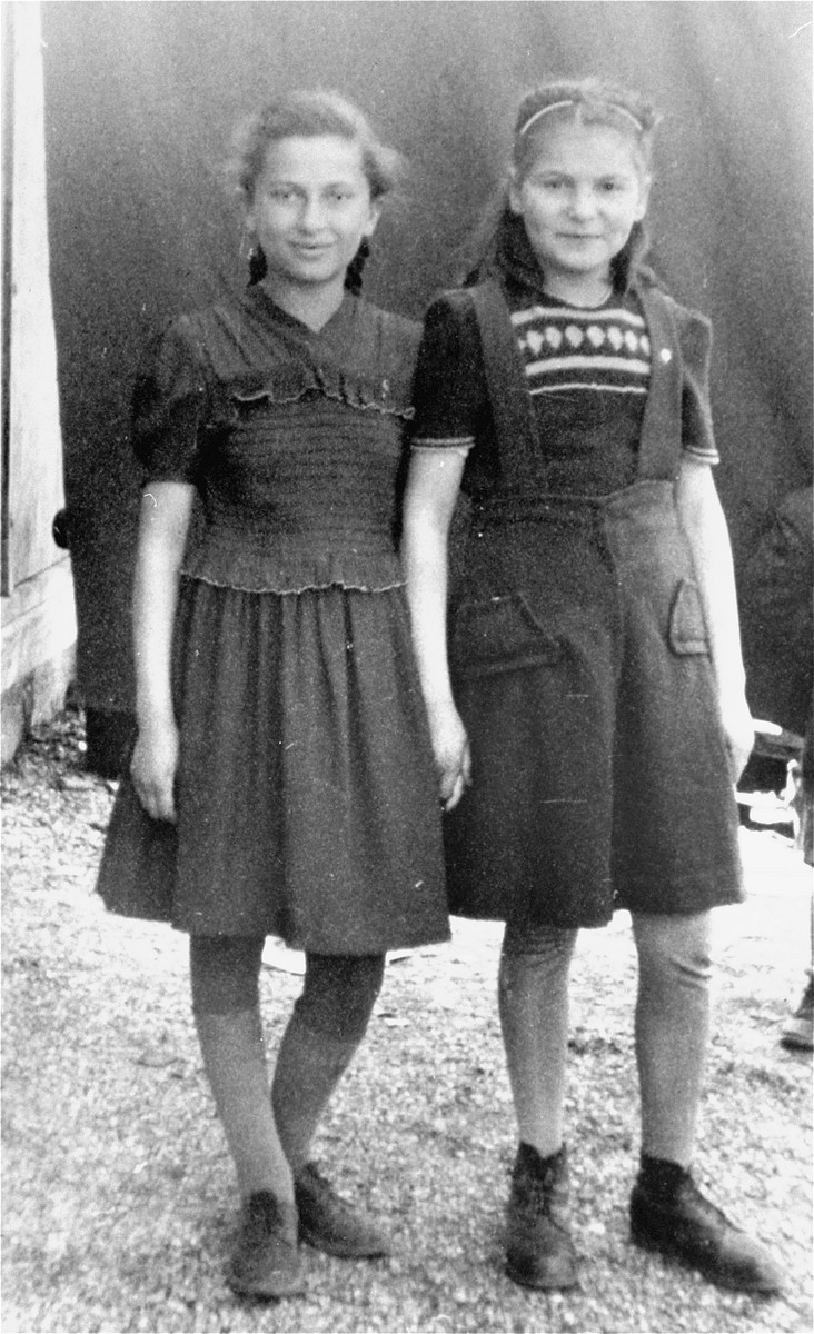 Frima Gleiser (right) and a friend stand outside a barrack in the Pocking (Schlupfing) displaced persons camp.