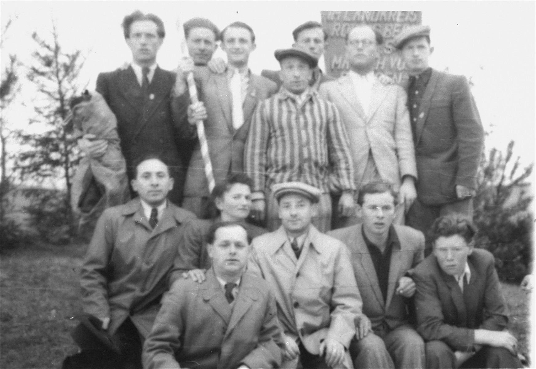 Jewish men, one in concentration camp uniform gather in the Pocking displaced persons camp.   Alexander Contract (third from left, back row) holds the Israeli flag.