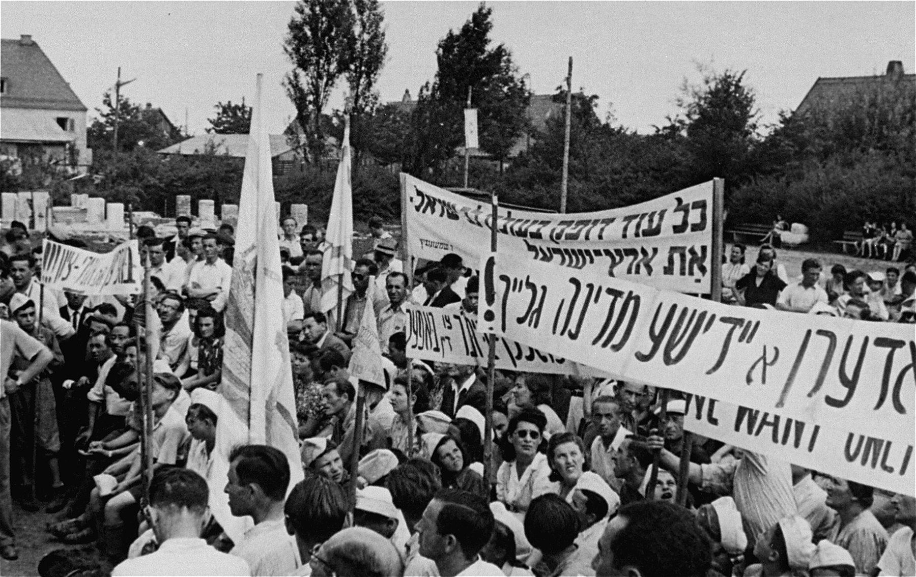 Jewish DPs hold flags and banners during a Zionist demonstration at the Neu Freimann displaced persons camp.  The banners in Hebrew and Yiddish call for the establishment of a Jewish state in Palestine.