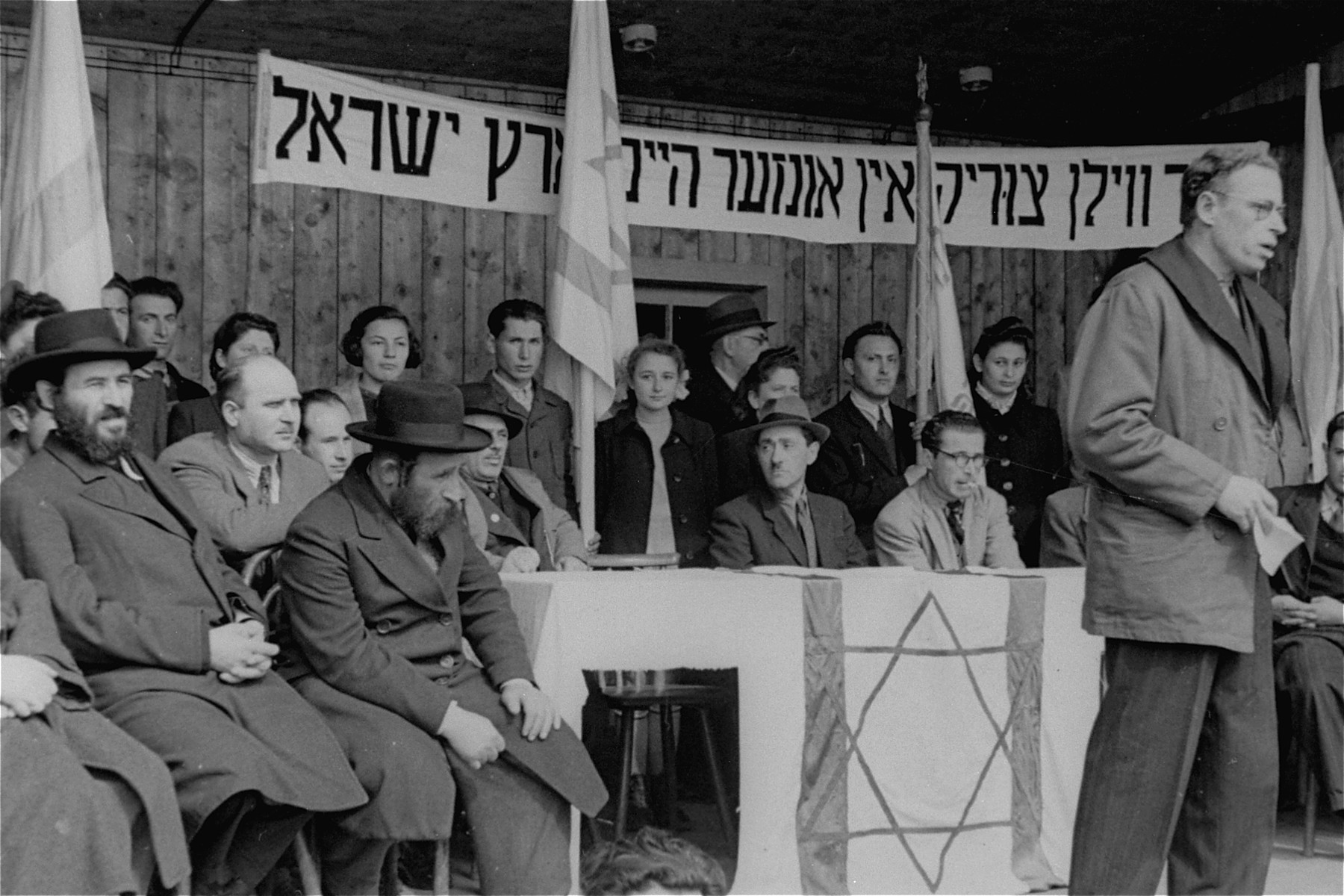 """Neu Freimann DP camp leader Siroka delivers a speech at a demonstration calling for unrestricted Jewish immigration to Palestine.  The text of the Yiddish banner reads: """"We want to go back to our home in the Land of Israel."""""""