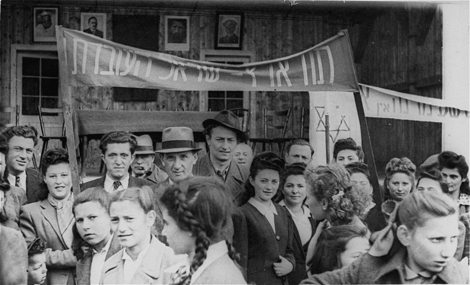 Jewish DPs participate in a demonstration calling for unrestricted immigration to Palestine at the Neu Freimann displaced persons camp.  The second person from the left is Lilly Scherb (maiden name, Kleidermacher, who was the aunt of Aaron Elster. The little boy just below her elbow is her baby brother who later was run over by a truck and killed in the camp. The young ladies in front were fellow schoolmates of Aaron.