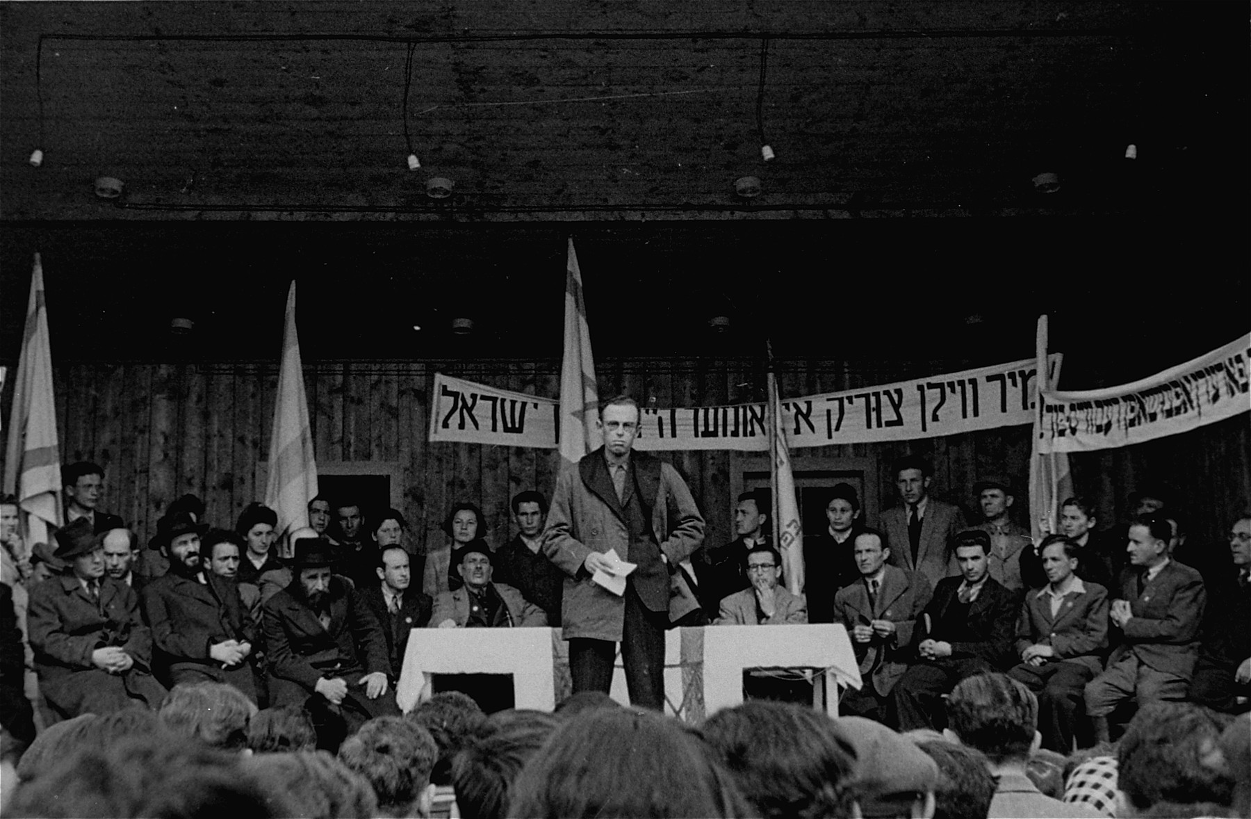 "DP camp leader Siroka addresses the crowd at a Zionist demonstration in the Neu Freimann displaced persons camp.  The text of the Yiddish banner reads: ""We want to go back to our home in the Land of Israel."""