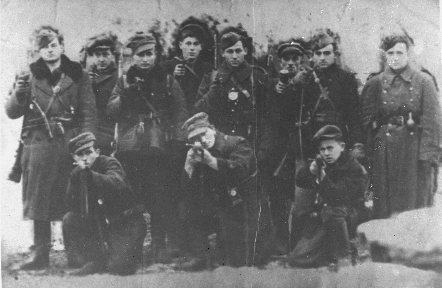 Group portrait of members of the Jewish partisan unit commanded by Yehiel Grynszpan in the Parczew Forest.    Standing from left to right are: Dudkin Rubinstein, Jurek Pomeranc, Lonka Pfefferkorn, Lova ?, and Yehiel Grynszpan.  Kneeling at the right is Pacan Rubinstein.