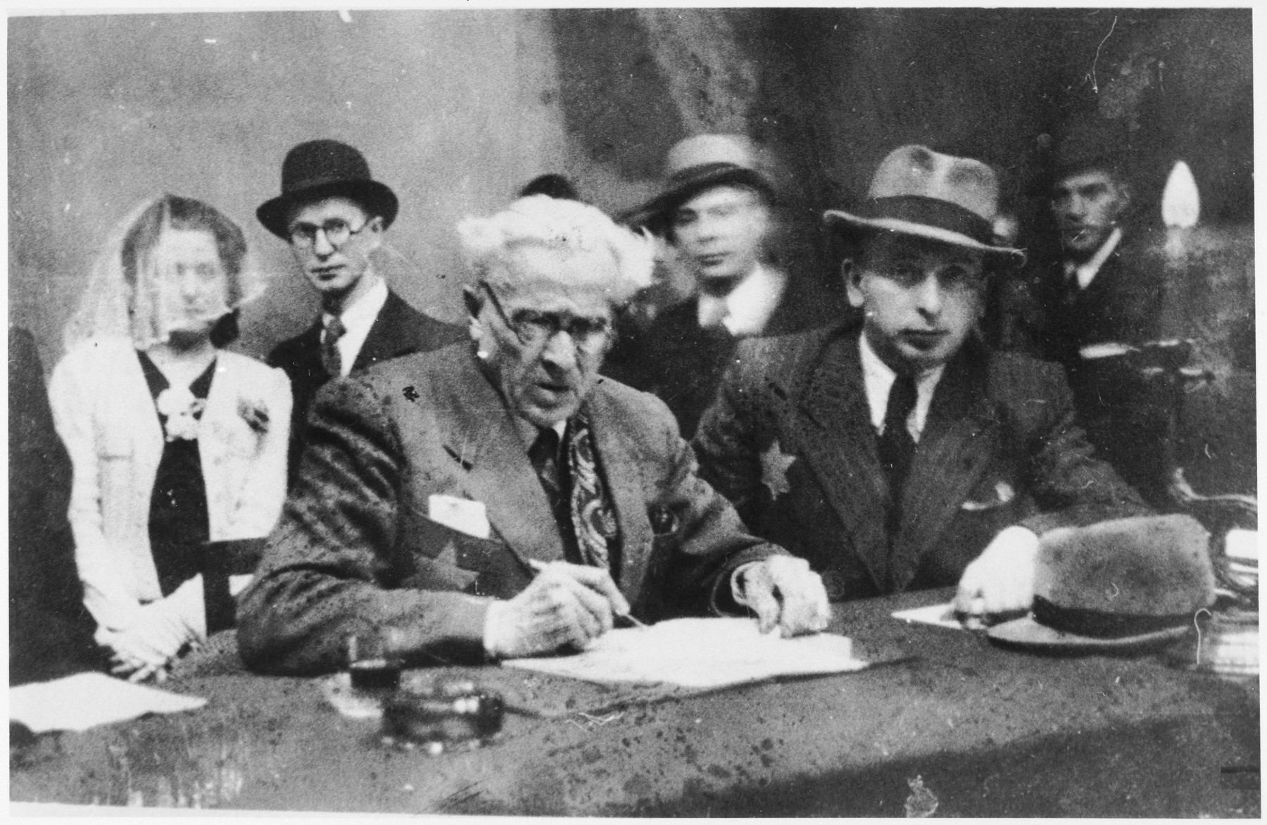 Jewish council chairman Mordechai Chaim Rumkowski signs a document at a wedding in the Lodz ghetto.  Pictured on the right is Sucher Erlich.  He survived the Holocaust.