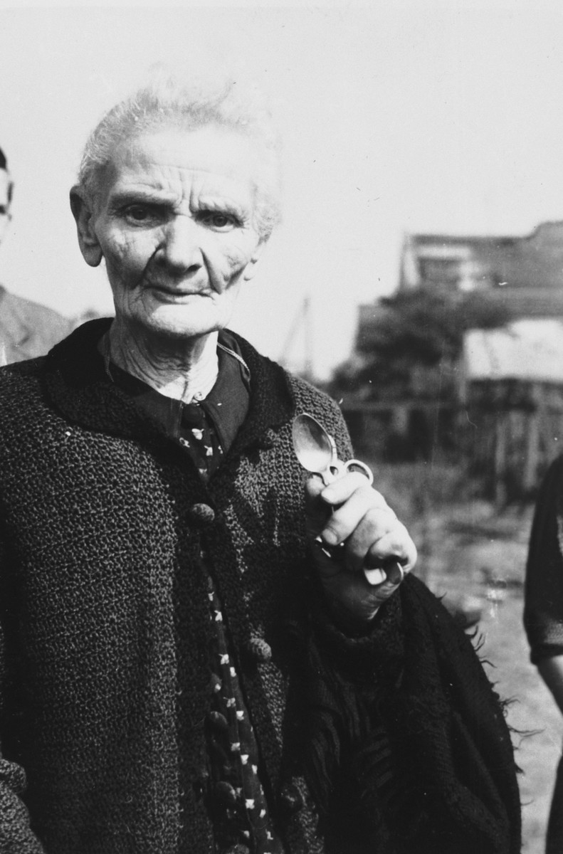 An elderly Polish woman poses with two silver spoons and a pair of scissors, all that remained of her home after it was destroyed in a German air raid during the siege of Warsaw.  The woman's name is Mrs. Jaworska.  Julien Bryan later learned that she died in 1940.