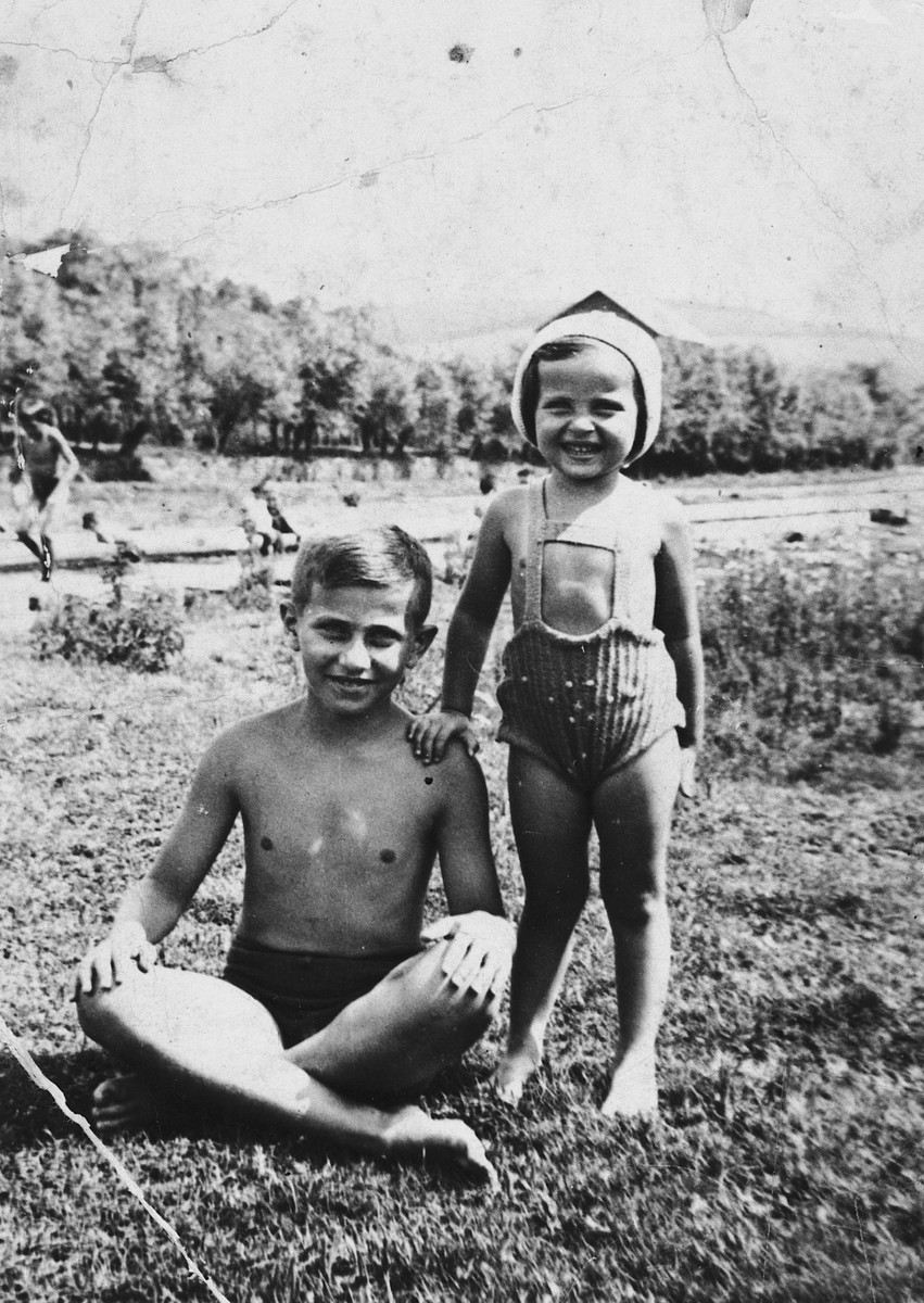 A brother and sister pose in their bathing suits by a river near Lvov.  Pictured are Shlomo and Charlotte Kohn.