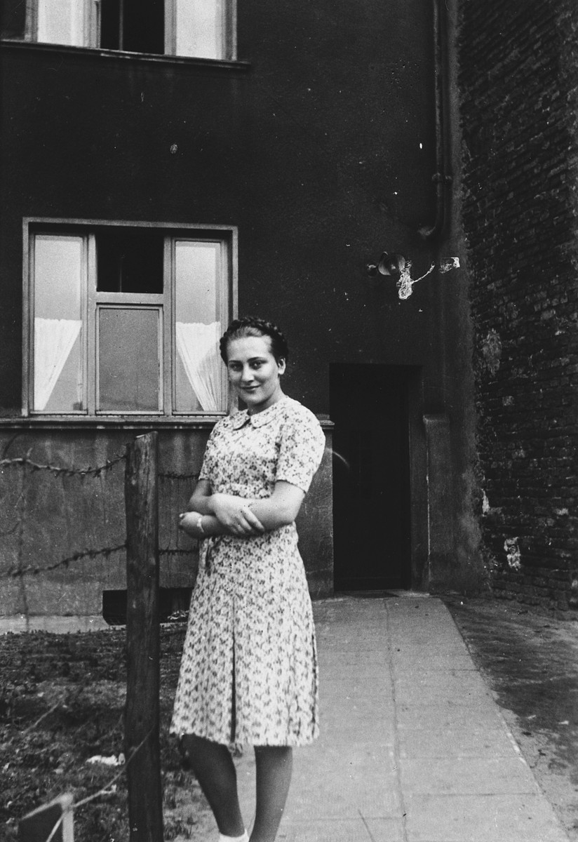 """Mania Baum stands next to a barbed wire fence in front of an apartment building in the Bedzin ghetto.  The photograph is inscribed """"To sweet Genia, as a memento, Mania."""""""