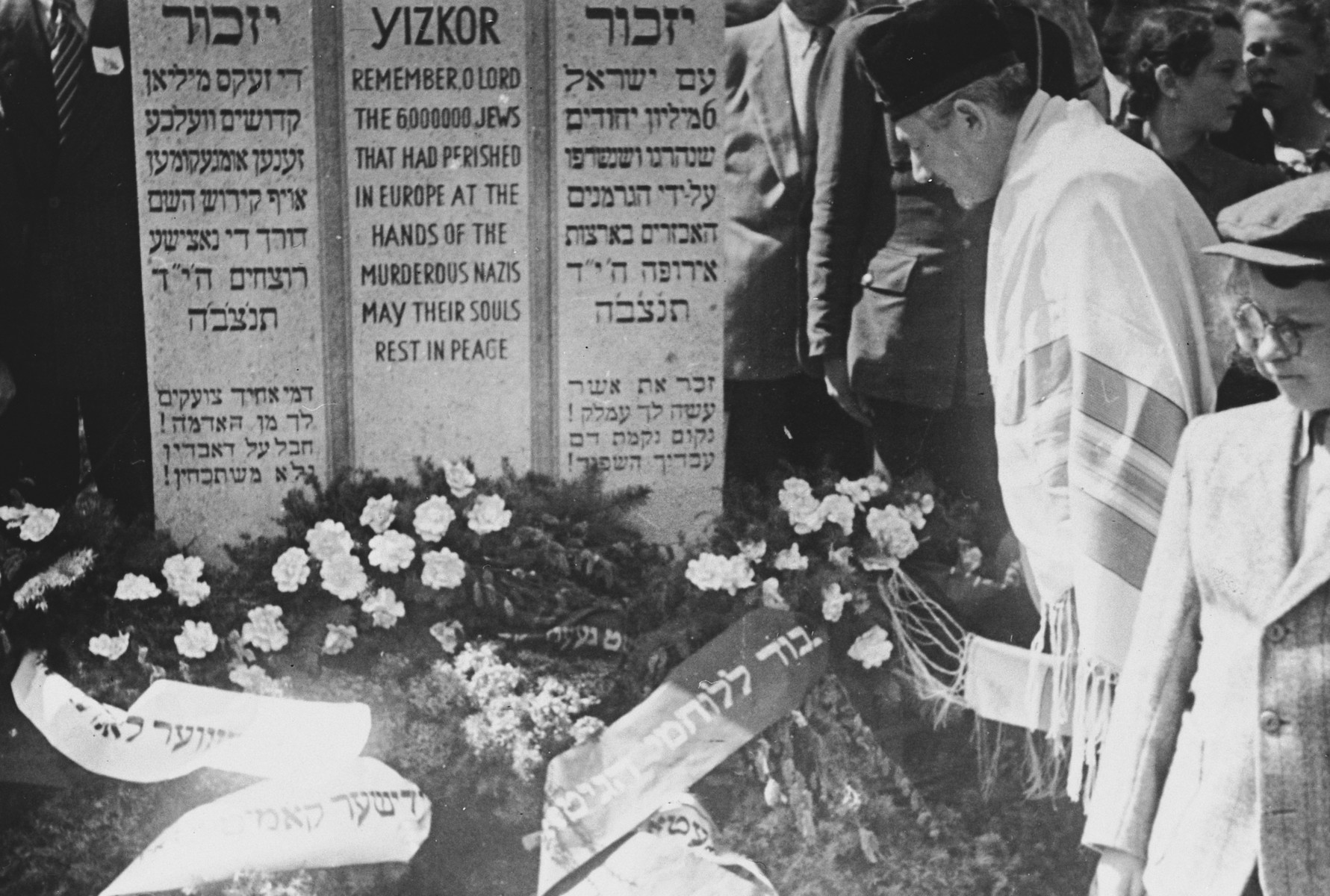 Cantor Pinchos Rabinowitz, clad in a large prayer shawl, offers prayers in front of a memorial to the victims of the Holocaust adorned with wreaths of flowers.